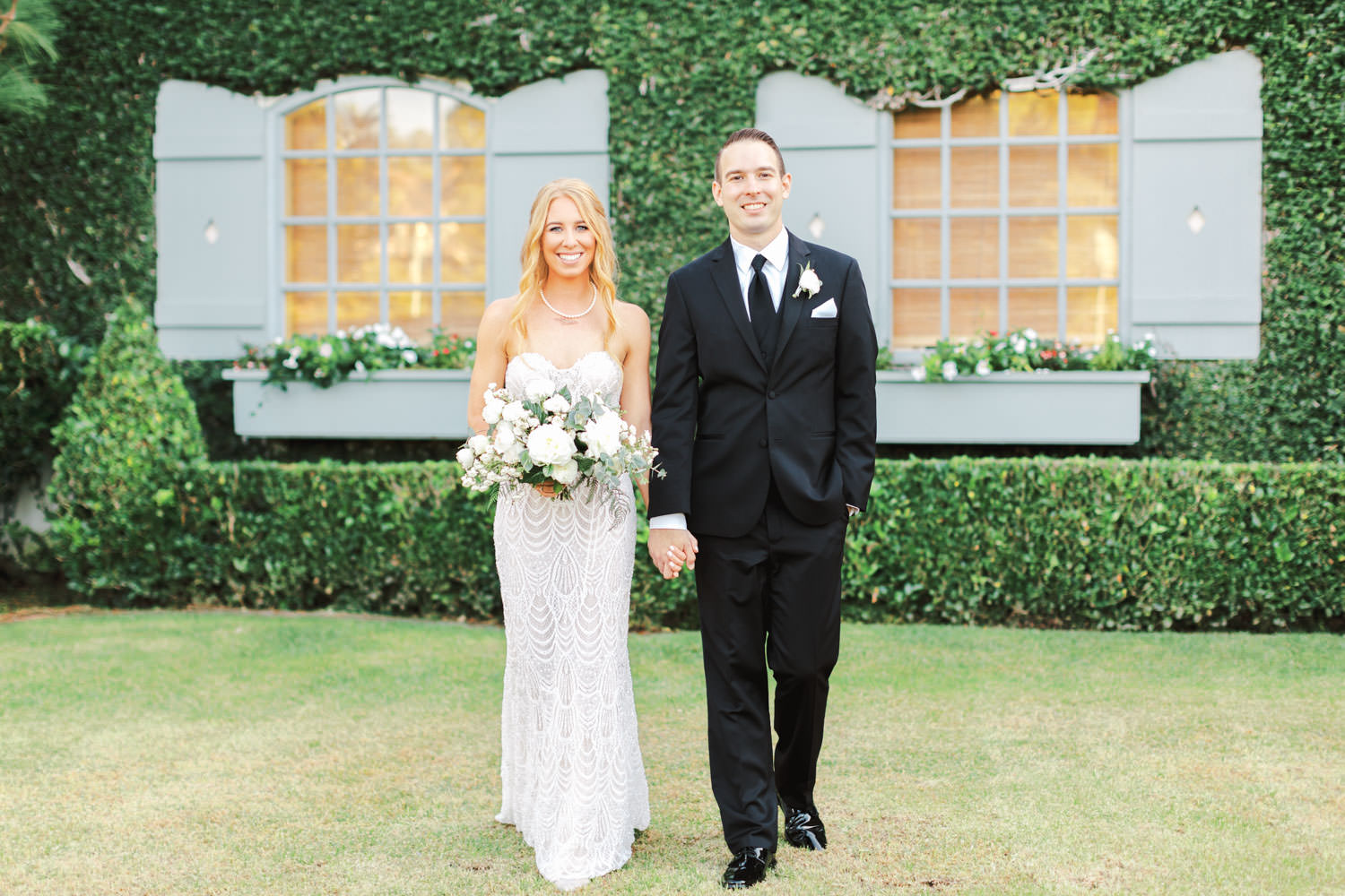 Bride and groom in front of an ivy-covered building with blue shutters. Bride wearing a Galia Lahav Gala gown with a sweetheart neckline carrying an ivory and green bouquet. Del Mar Country Club Wedding by Cavin Elizabeth Photography
