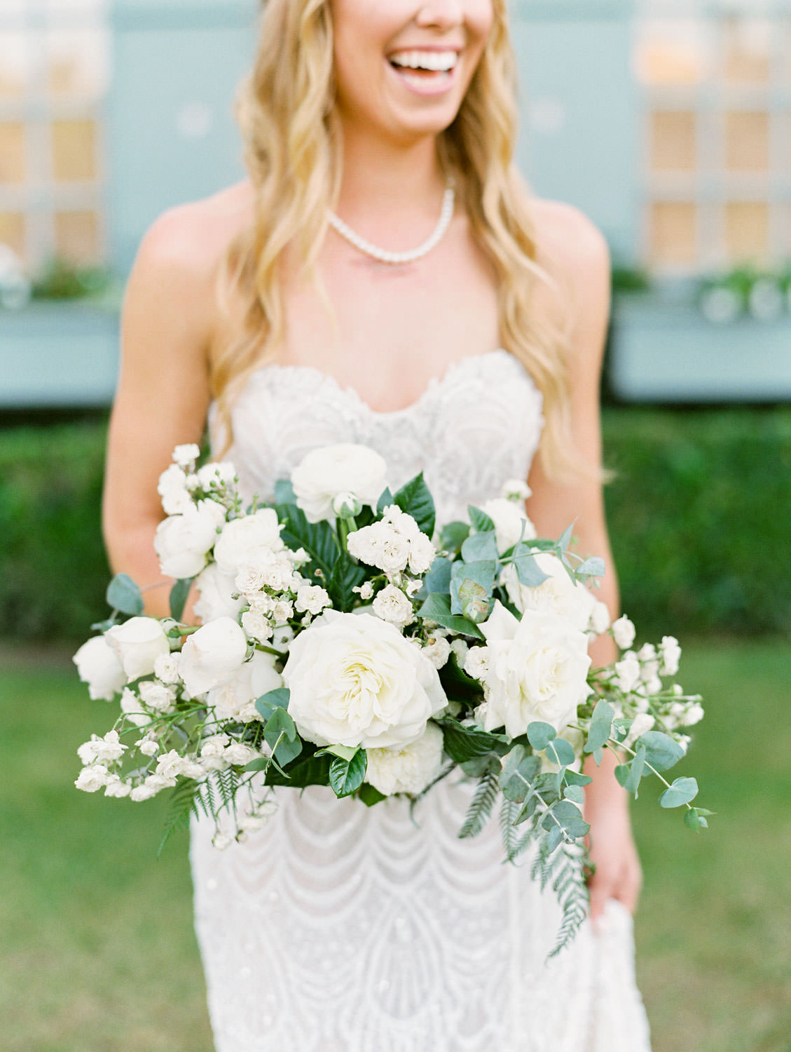 Bride shot on film in front of an ivy-covered building with blue shutters. Bride wearing a Galia Lahav Gala gown with a sweetheart neckline carrying an ivory and green bouquet. Del Mar Country Club Wedding by Cavin Elizabeth Photography