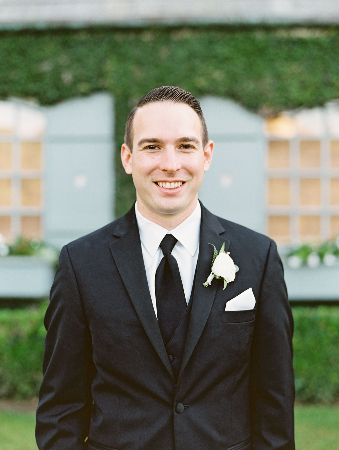 Groom shot on film wearing a black tuxedo with vest and ivory boutonniere. Del Mar Country Club Wedding by Cavin Elizabeth Photography