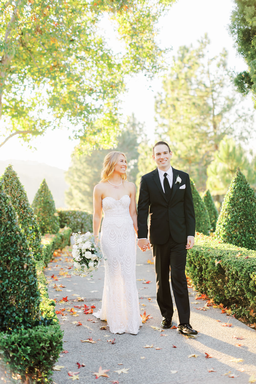 Bride and groom walking down a path of hedges. Bride wearing a Galia Lahav Gala gown with a sweetheart neckline carrying an ivory and green bouquet. Del Mar Country Club Wedding by Cavin Elizabeth Photography