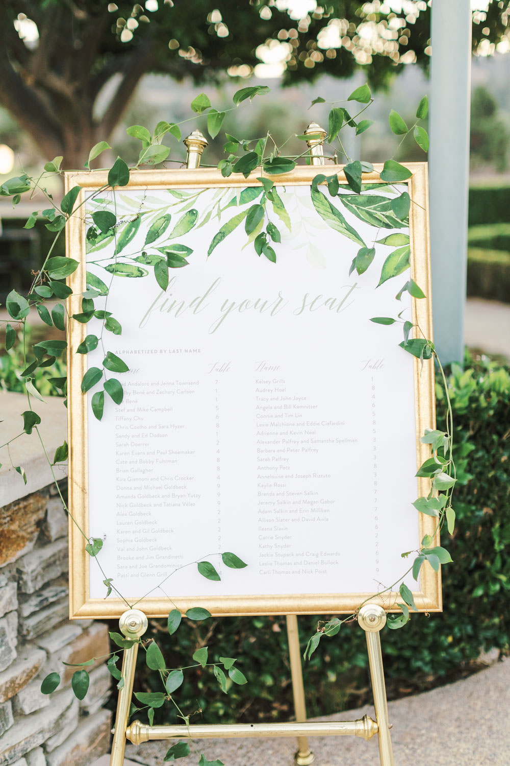 Guest seating chart printed on ivory poster covered in digital and real greenery in a gold frame. Del Mar Country Club Wedding by Cavin Elizabeth Photography