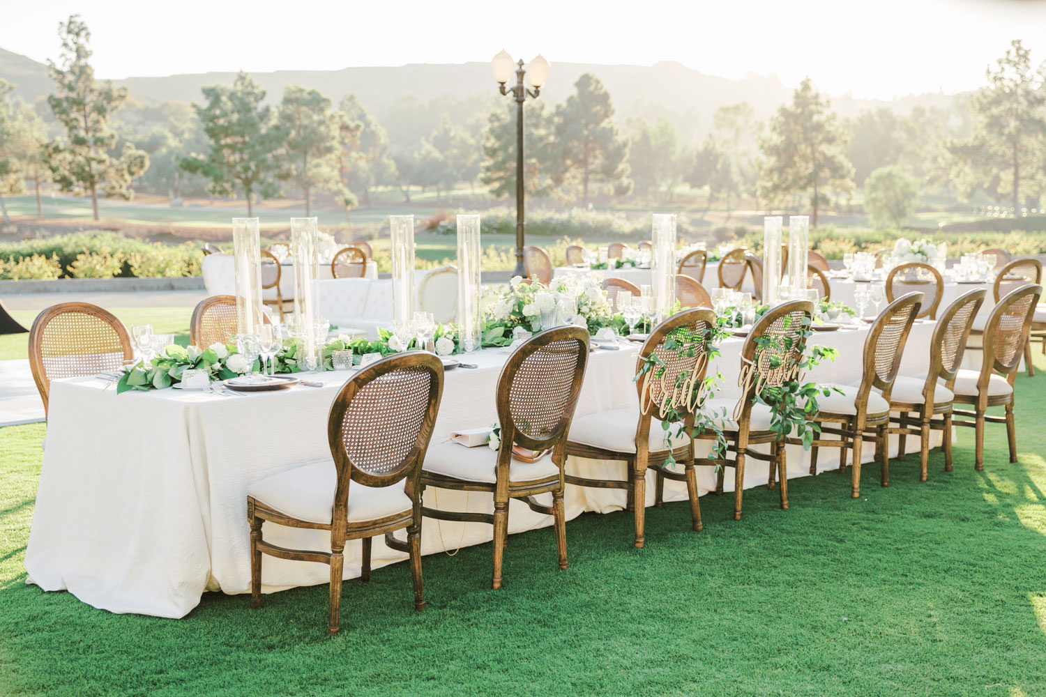 Film photo of an al fresco reception on a golf lawn with a mix of round and long tables covered in ivory linens. Oak Louis cane back chairs and white and green centerpieces by Compass Floral and Luxe Events. Del Mar Country Club Wedding by Cavin Elizabeth Photography