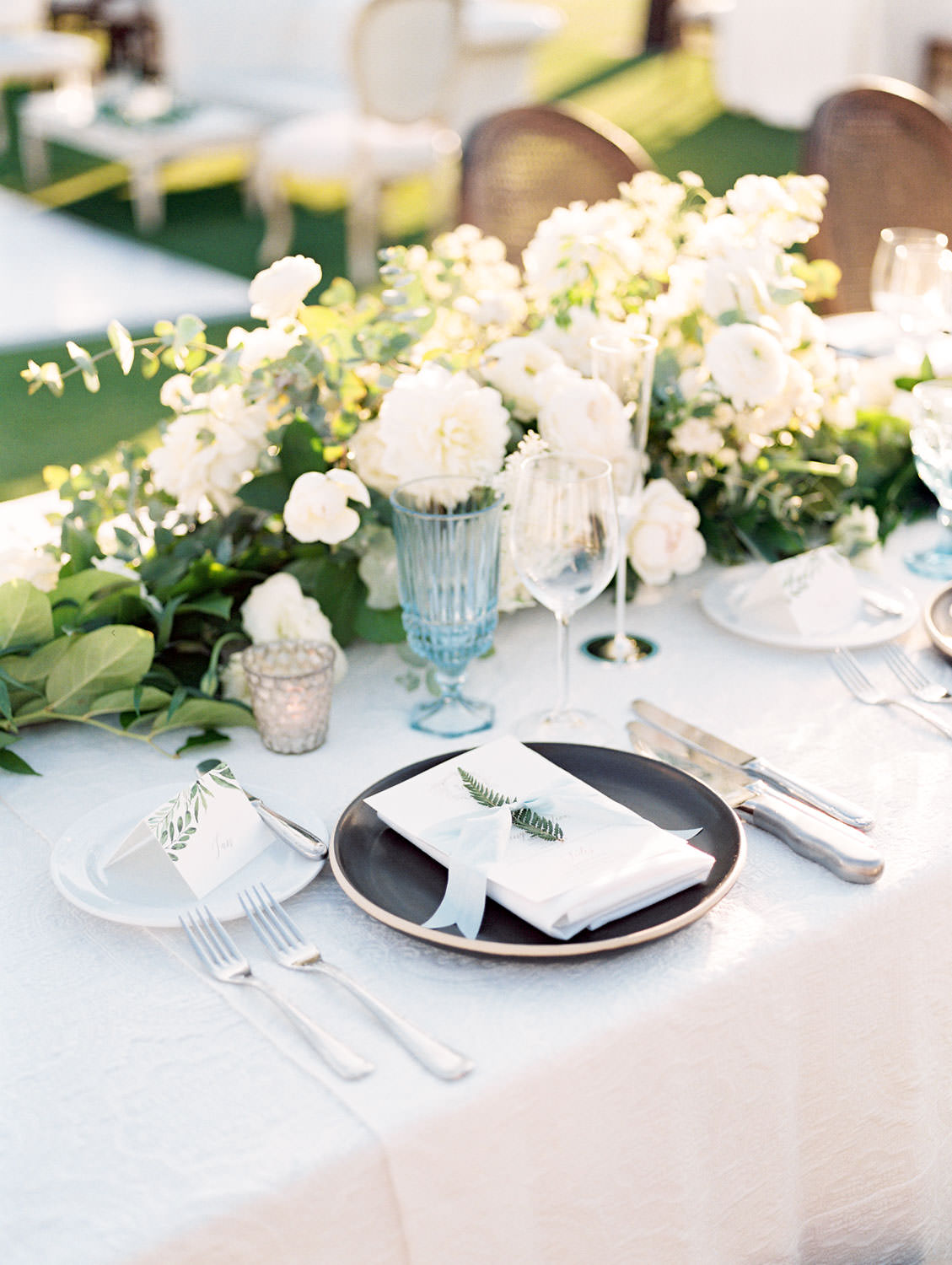Film photo of an al fresco reception on a golf lawn. Place setting with blue and crystal glassware, black chargers, and ivory menus with a sprig of greenery. White and green centerpieces by Compass Floral and Luxe Events. Del Mar Country Club Wedding by Cavin Elizabeth Photography