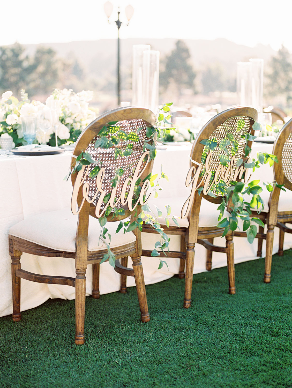 Film photo of an al fresco reception on a golf lawn with a mix of round and long tables covered in ivory linens. Oak Louis cane back chairs with wooden laser cut bride and groom signs and white and green centerpieces by Compass Floral and Luxe Events. Del Mar Country Club Wedding by Cavin Elizabeth Photography