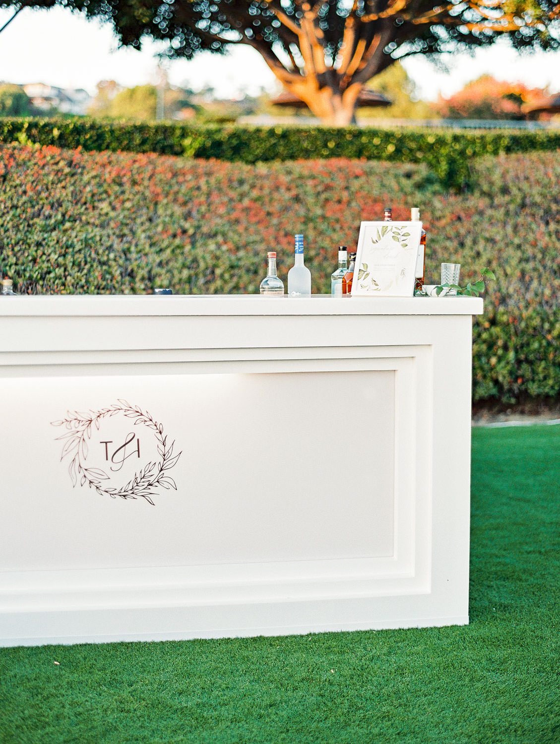 Film photo of an al fresco reception custom white bar with couple's logo planned by Luxe Events. Del Mar Country Club Wedding by Cavin Elizabeth Photography