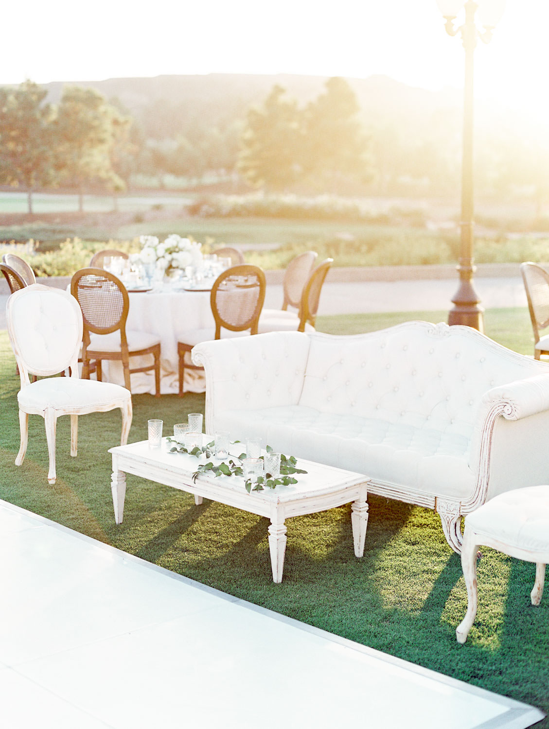 Film photo of an al fresco reception white lounge with sofa, chairs, and coffee table planned by Luxe Events. Del Mar Country Club Wedding by Cavin Elizabeth Photography