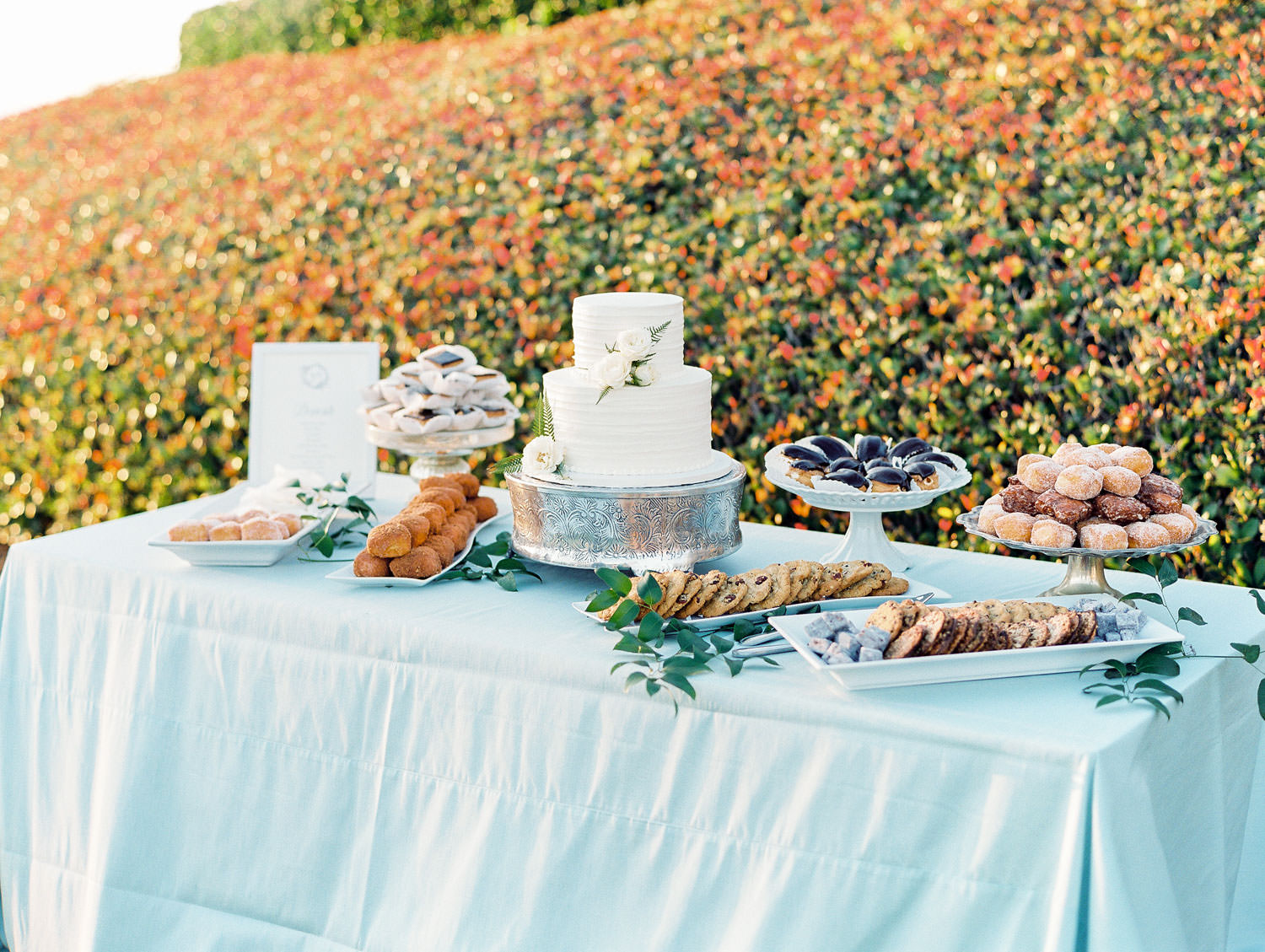 Film photo of an al fresco reception dessert table with blue linen, white two tier cake, and several small desserts planned by Luxe Events. Del Mar Country Club Wedding by Cavin Elizabeth Photography