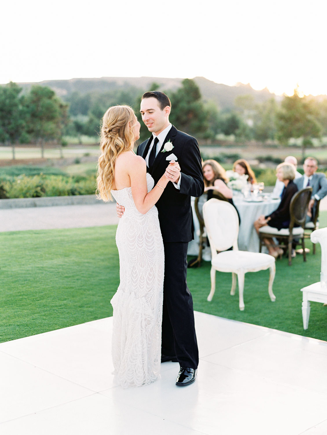 Film photo of an al fresco reception first dance with bride and groom on a white dance floor. Del Mar Country Club Wedding by Cavin Elizabeth Photography
