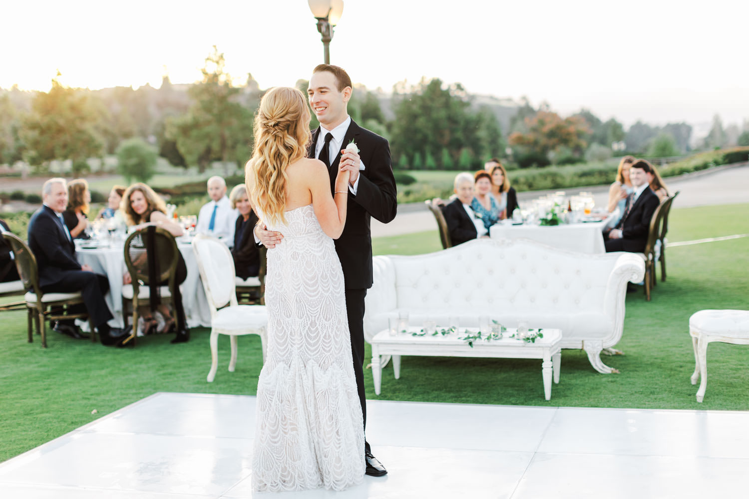 Photo of an al fresco reception first dance with bride and groom on a white dance floor. Del Mar Country Club Wedding by Cavin Elizabeth Photography