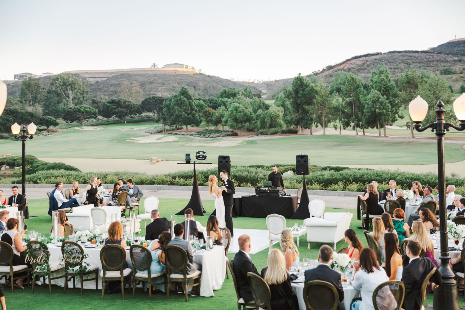 First dance wide photo of an al fresco reception on a golf lawn with a mix of round and long tables covered in ivory linens. Oak Louis cane back chairs and white and green centerpieces by Compass Floral and Luxe Events. Del Mar Country Club Wedding by Cavin Elizabeth Photography