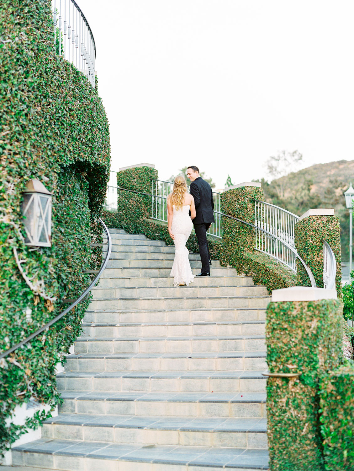 Film photo of bride and groom walking up stairs of an ivy-covered building. Bride wearing a Galia Lahav Gala gown with a sweetheart neckline. Del Mar Country Club Wedding by Cavin Elizabeth Photography