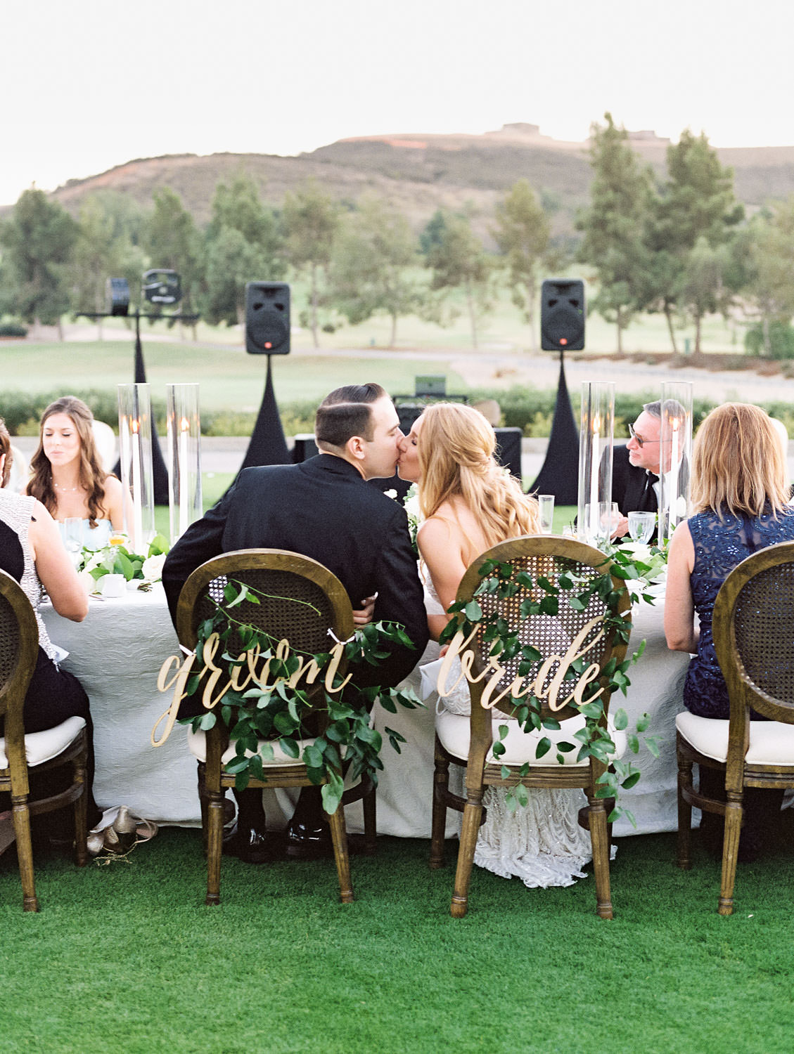 Film photo of an al fresco reception with bride and groom kissing in their seats. Oak Louis cane back chair with laser cut bride and groom signs. Del Mar Country Club Wedding by Cavin Elizabeth Photography