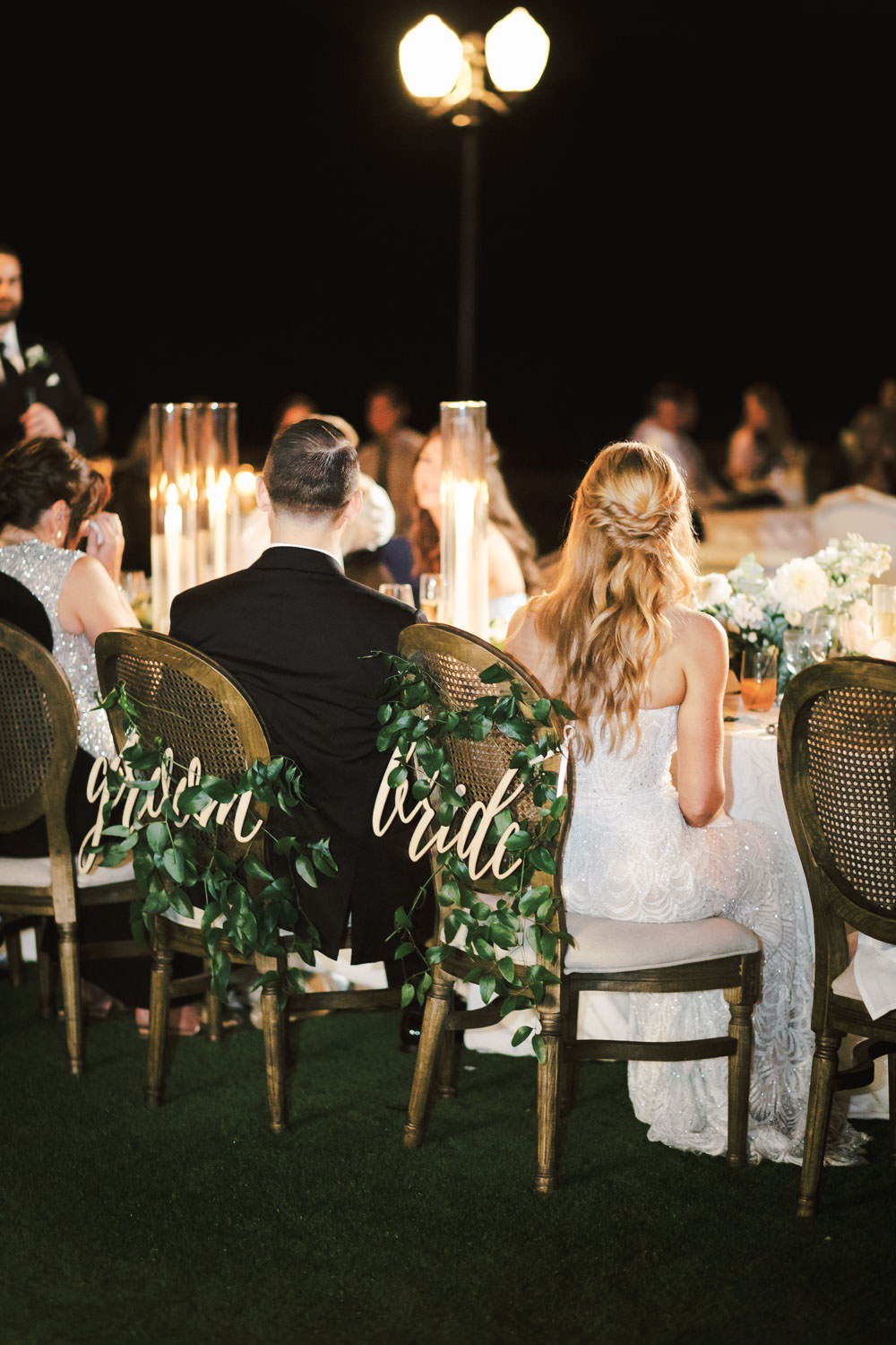 Reception photo of bride and groom during toasts. Oak Louis cane back chair with laser cut bride and groom signs. Del Mar Country Club Wedding by Cavin Elizabeth Photography