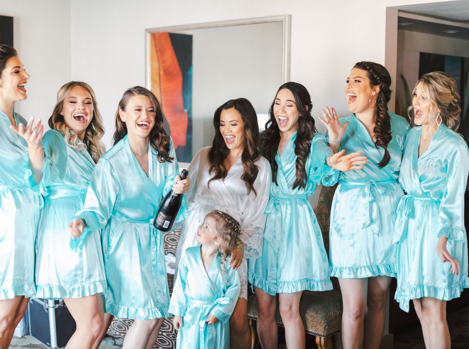 Bridal party with turquoise silk robes and bride in white robe popping champagne, Wedding at Humphreys Half Moon Inn by Cavin Elizabeth Photography