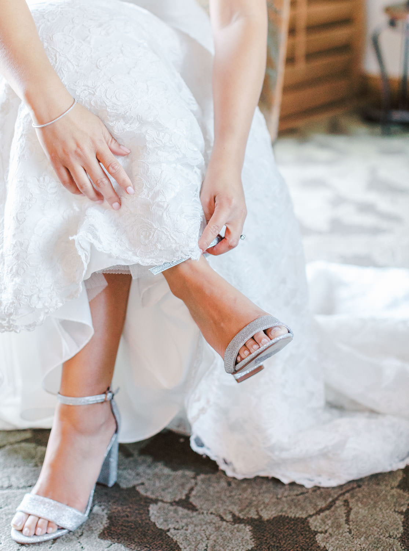 Bride putting on silver Sam Edelman pumps with glitter. Wedding at Humphreys Half Moon Inn by Cavin Elizabeth Photography