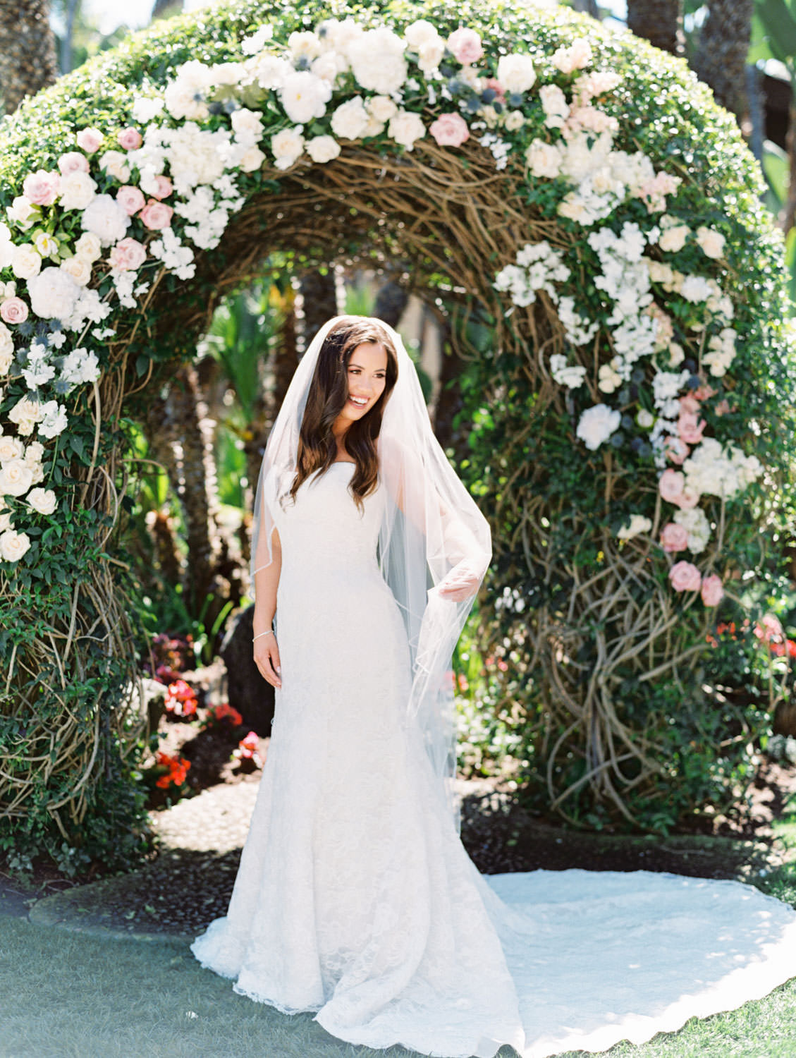 Bridal portrait with veil and train in front of floral arch on film. Wedding at Humphreys Half Moon Inn by Cavin Elizabeth Photography