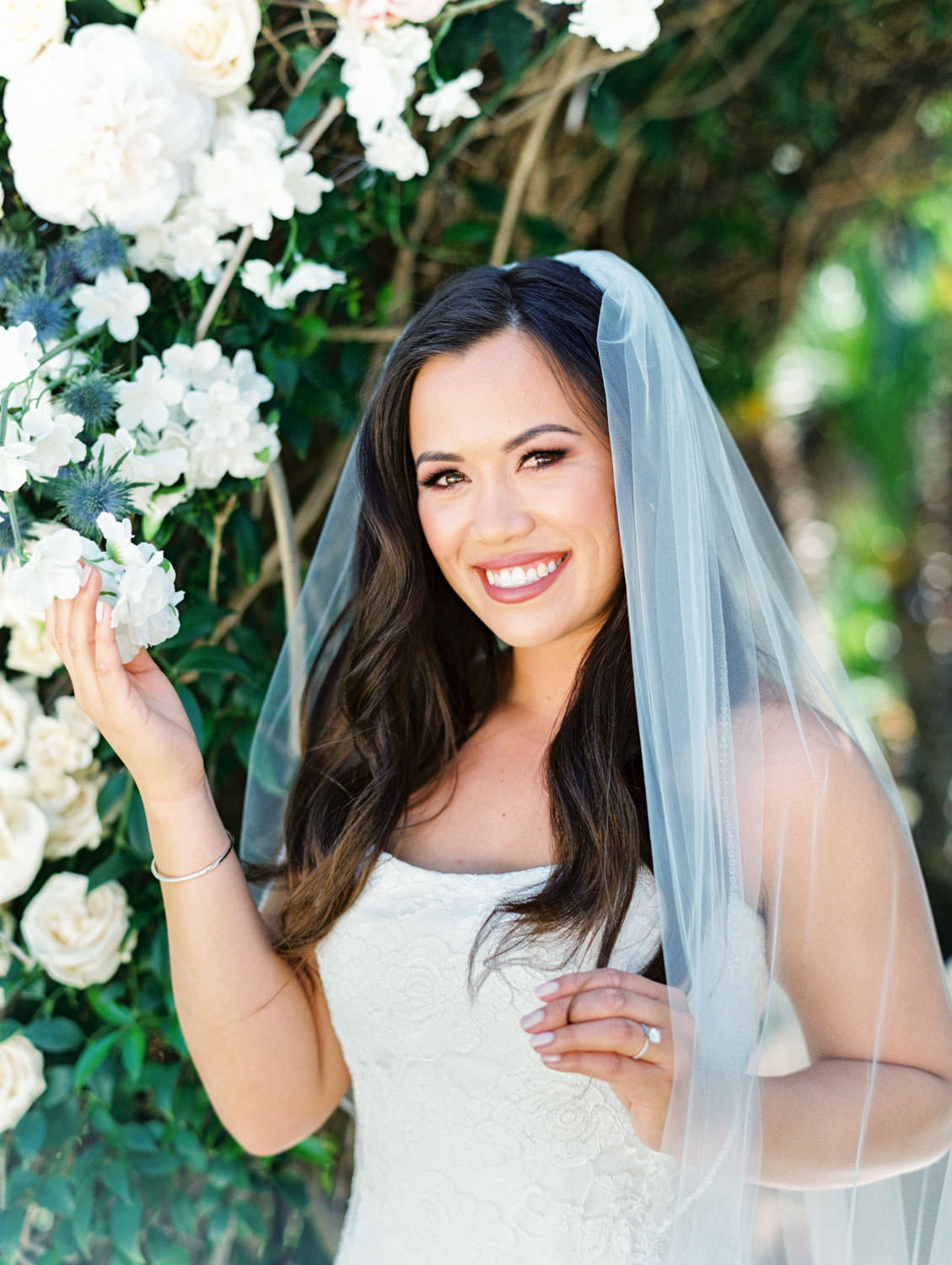 Bridal portrait with veil in front of floral arch on film. Wedding at Humphreys Half Moon Inn by Cavin Elizabeth Photography