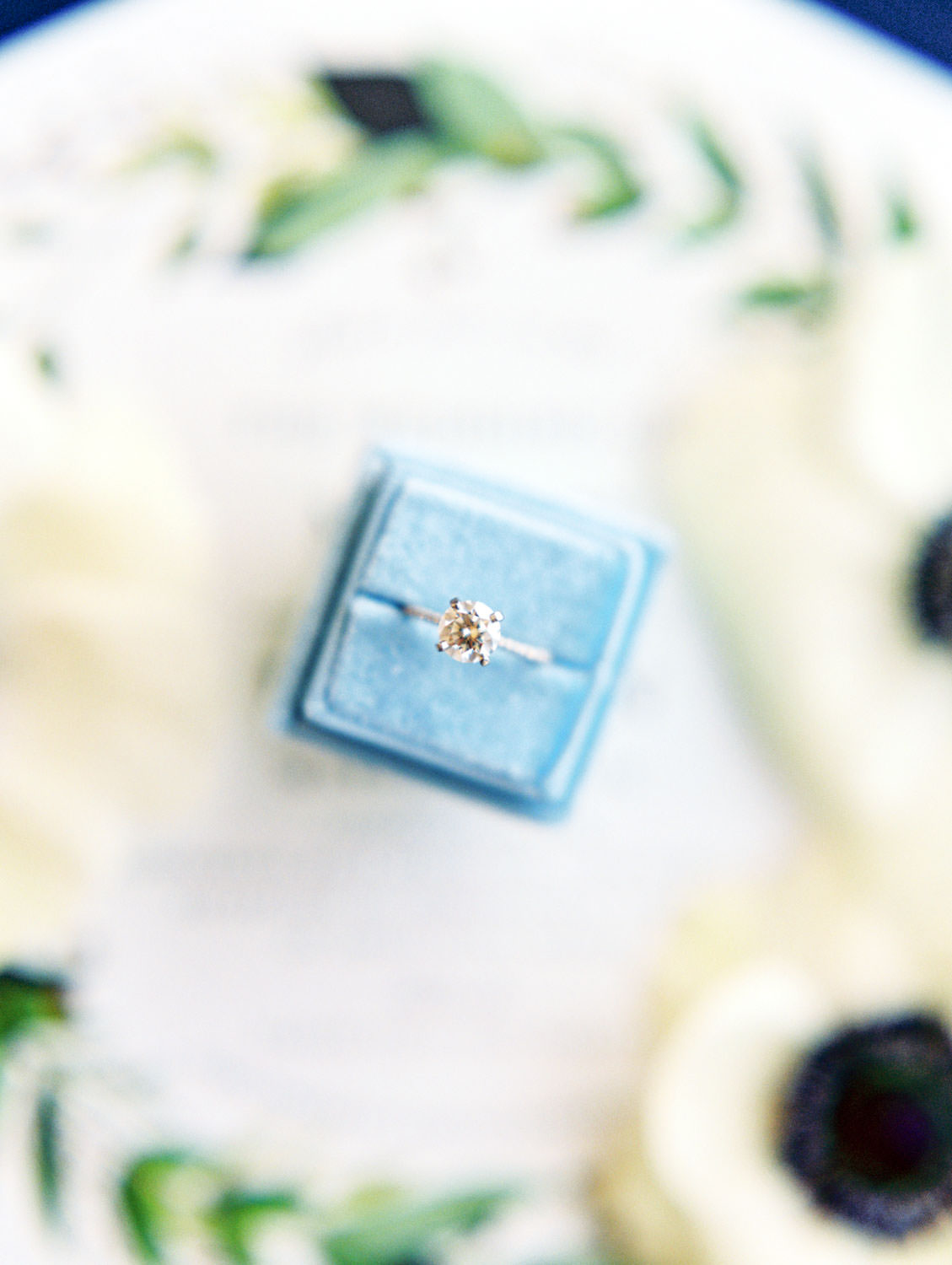Solitaire engagement ring in blue velvet ring box surrounded by anemones and invitation on film, Wedding at Humphreys Half Moon Inn by Cavin Elizabeth Photography