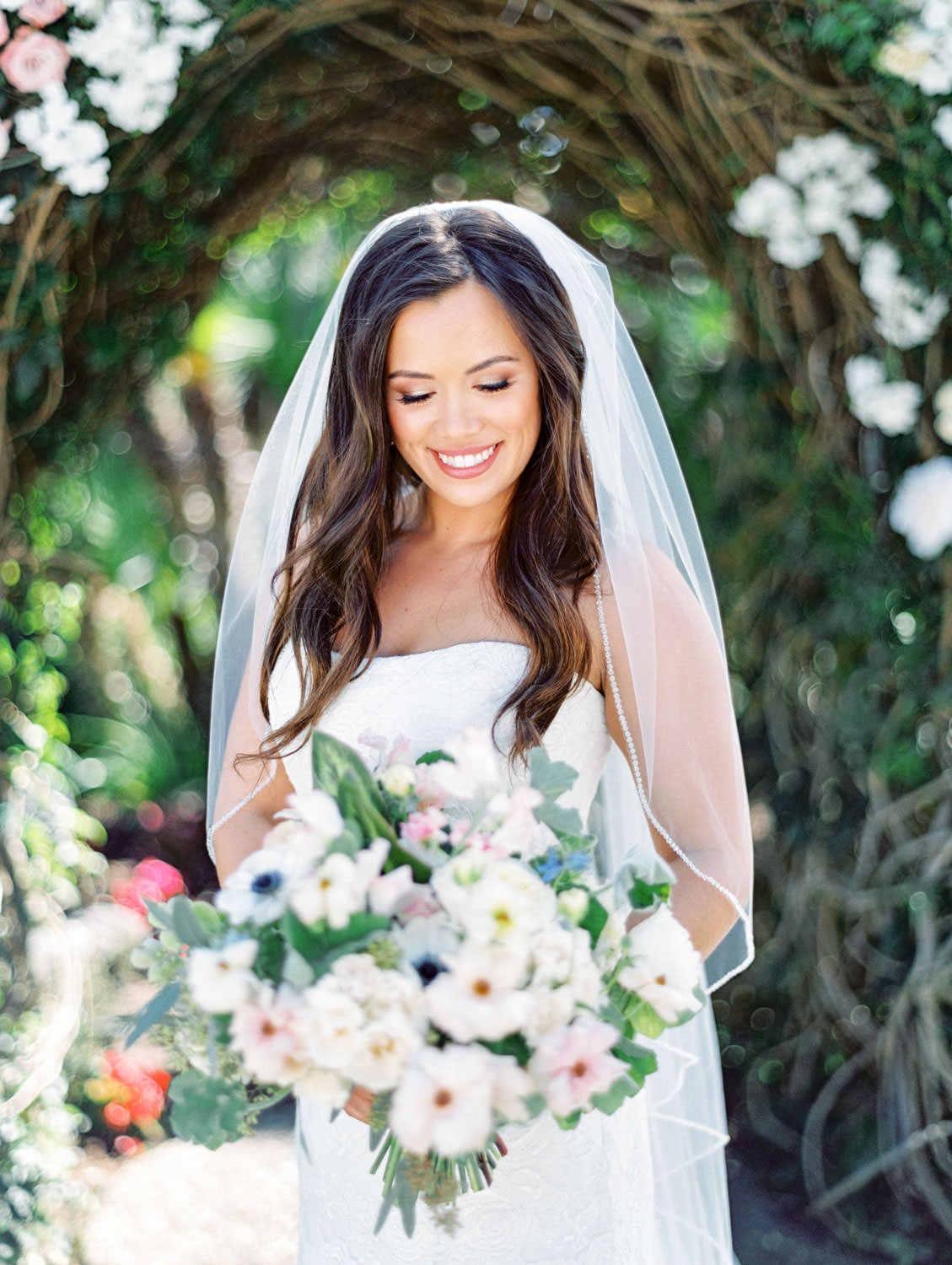 Bridal portrait with veil and train in front of floral arch on film. Bride's bouquet with anemones, greenery, and roses. Wedding at Humphreys Half Moon Inn by Cavin Elizabeth Photography