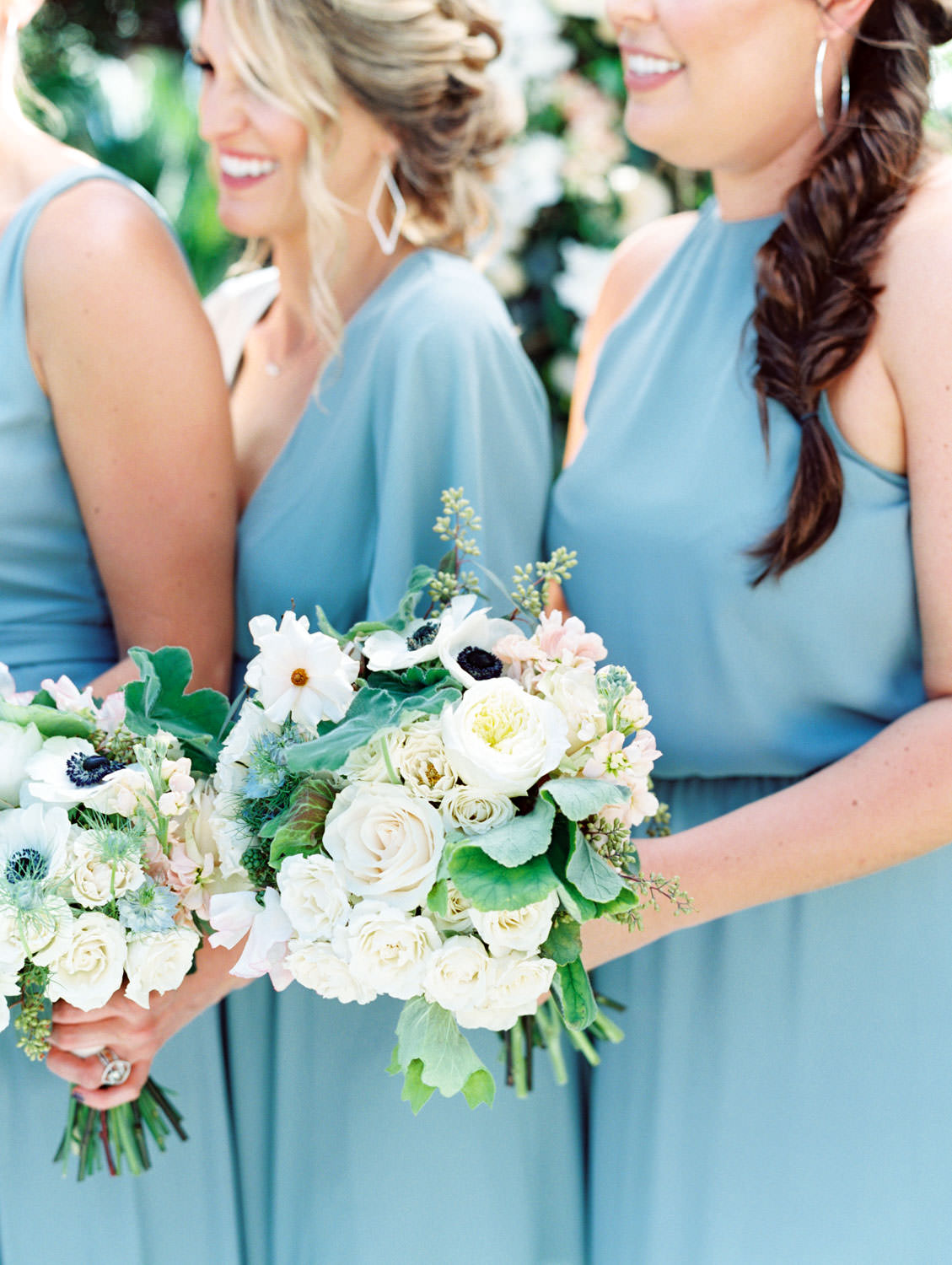 Bridesmaids in french blue dresses. Bouquets with anemones, greenery, ivory, and blush flowers in front of a large floral arch captured on film. Wedding at Humphreys Half Moon Inn by Cavin Elizabeth Photography