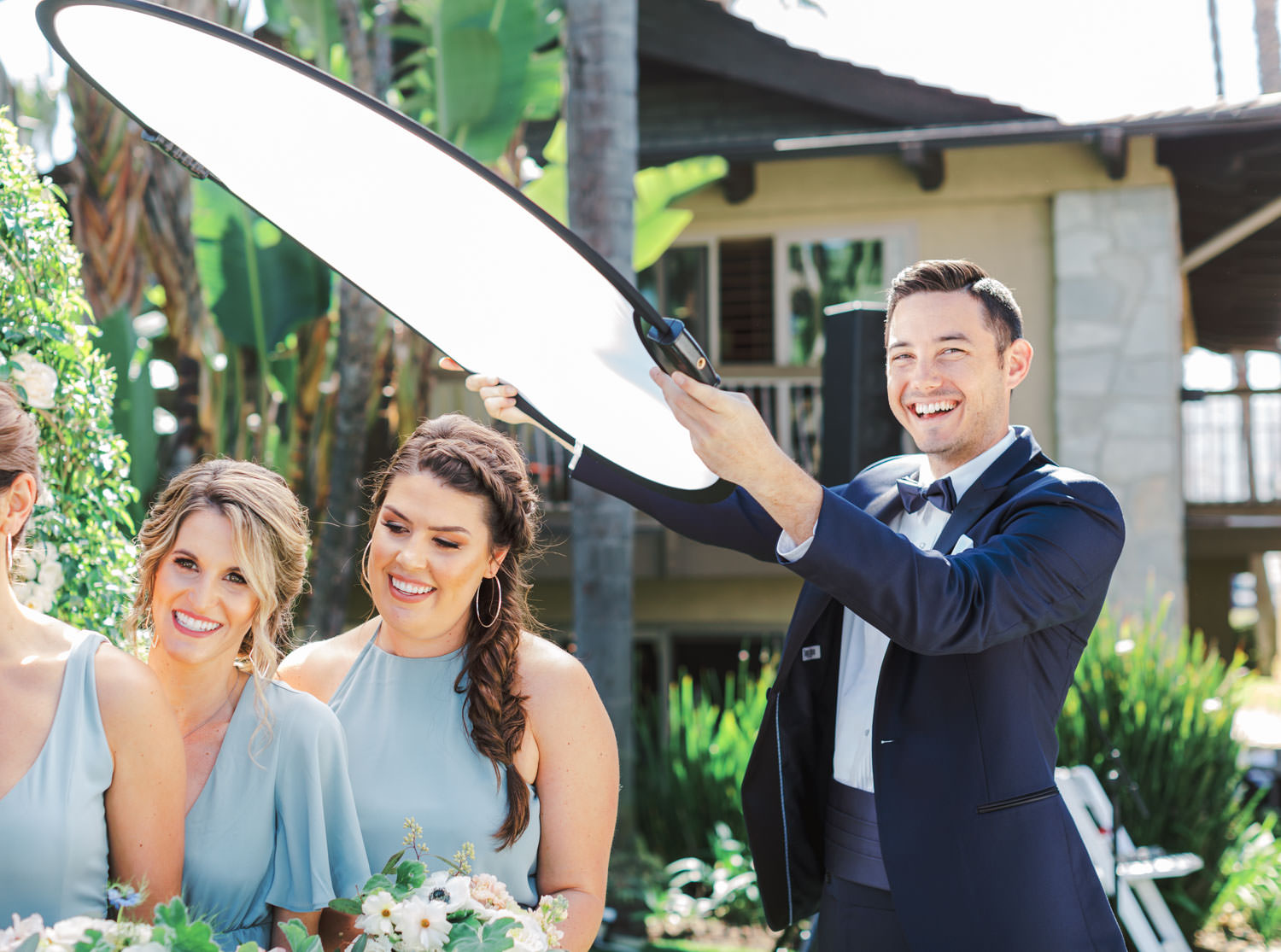Groomsman holding diffuser for bridal party photos. Cute behind the scenes wedding moments by Cavin Elizabeth Photography.