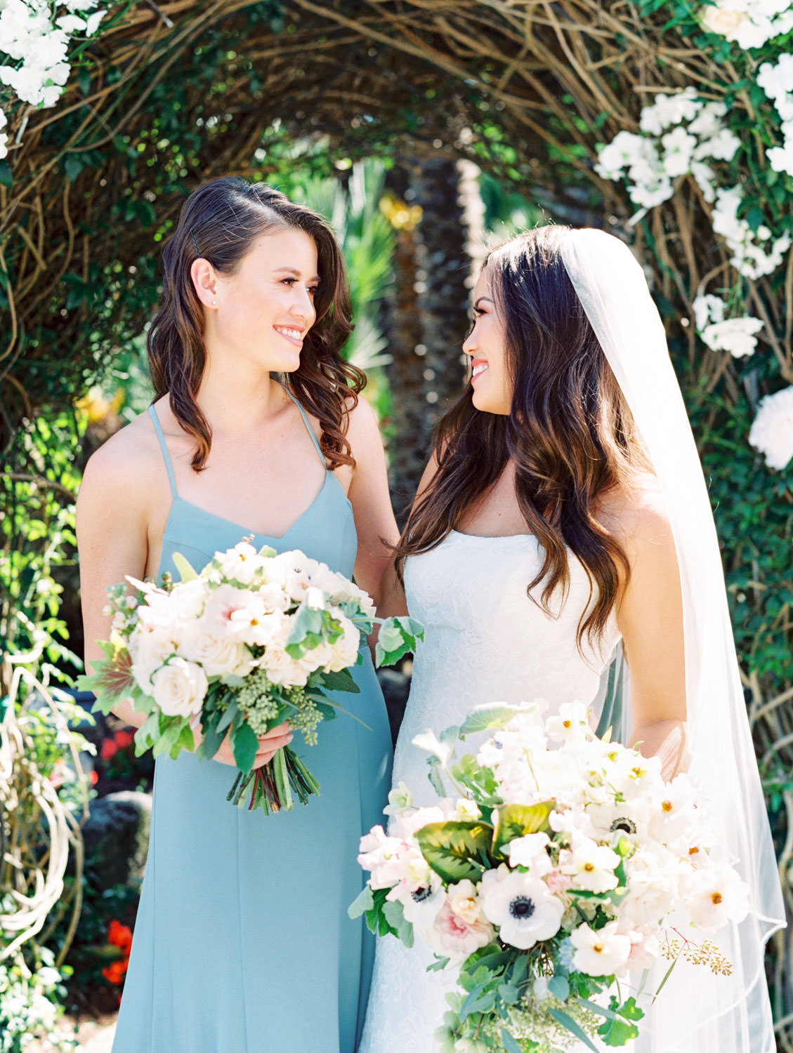 Bridesmaids in french blue dressed and bride in strapless lace gown. Bouquets with anemones, greenery, ivory, and blush flowers in front of a large floral arch captured on film. Wedding at Humphreys Half Moon Inn by Cavin Elizabeth Photography