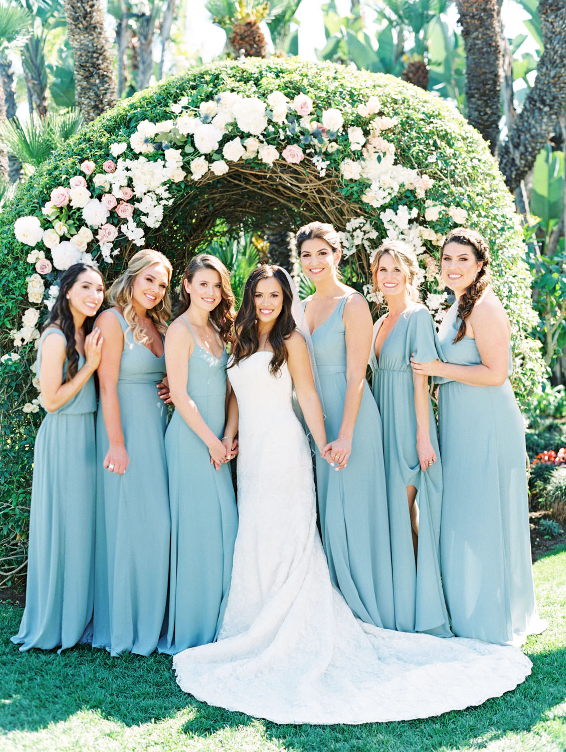 Bridesmaids in french blue dressed and bride in strapless lace gown. Bouquets with anemones, greenery, ivory, and blush flowers in a large floral arch captured on film. Wedding at Humphreys Half Moon Inn by Cavin Elizabeth Photography