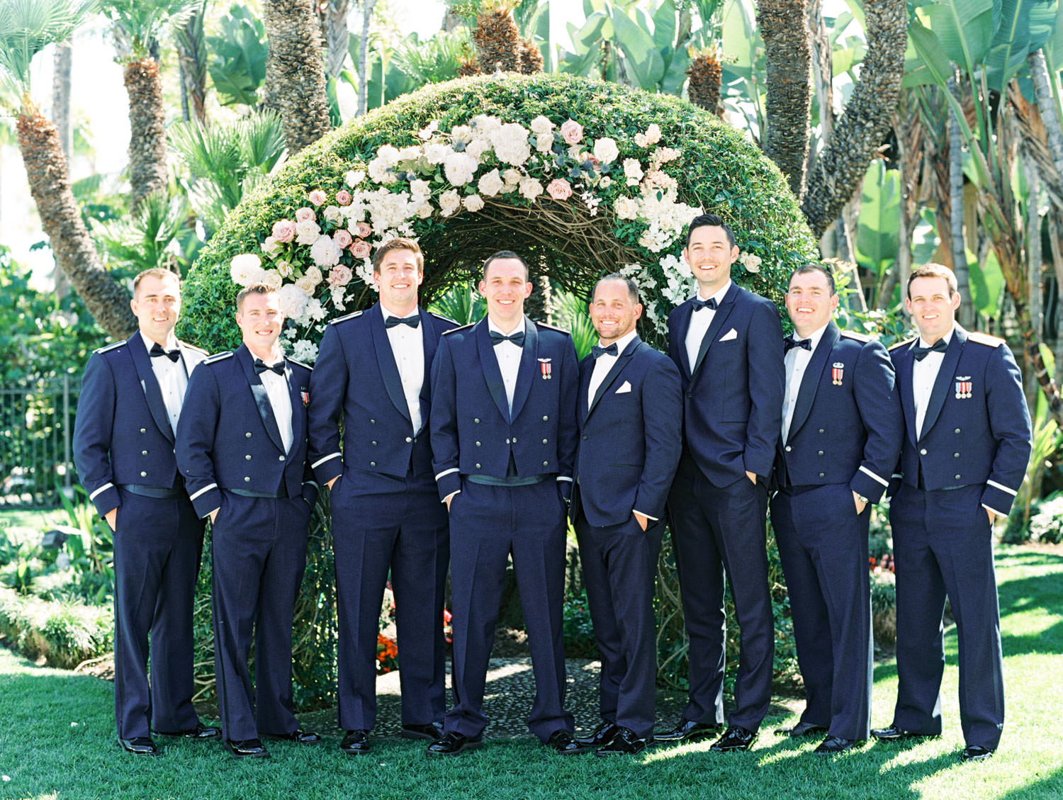 Groomsmen in air force and classic navy tuxedos in front of a large floral arch captured on film. Wedding at Humphreys Half Moon Inn by Cavin Elizabeth Photography