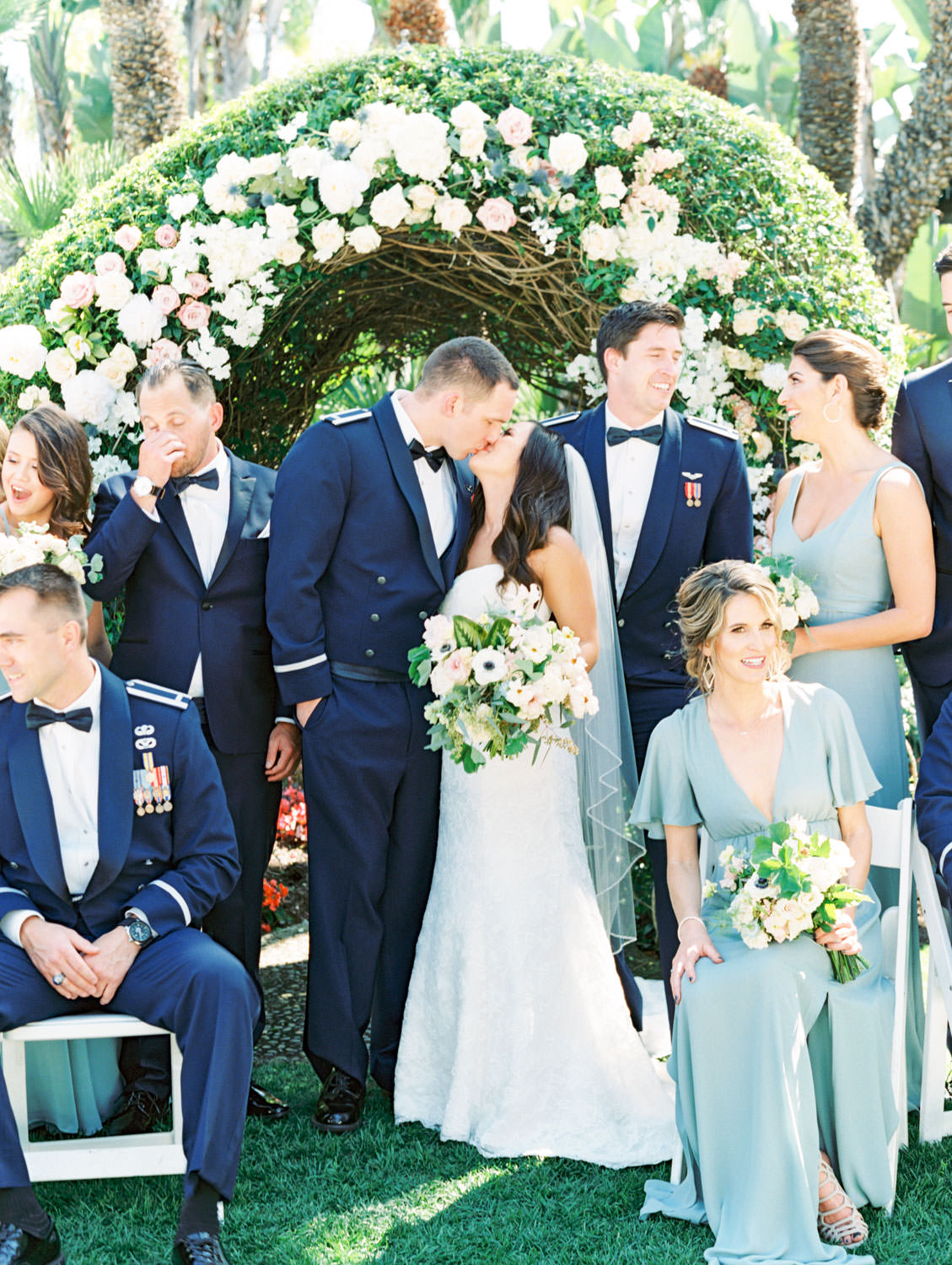 Bridesmaids in french blue dressed and bride in strapless lace gown with groom and groomsmen in air force tuxedos. Bouquets with anemones, greenery, ivory, and blush flowers in front of a large floral arch captured on film. Wedding at Humphreys Half Moon Inn by Cavin Elizabeth Photography