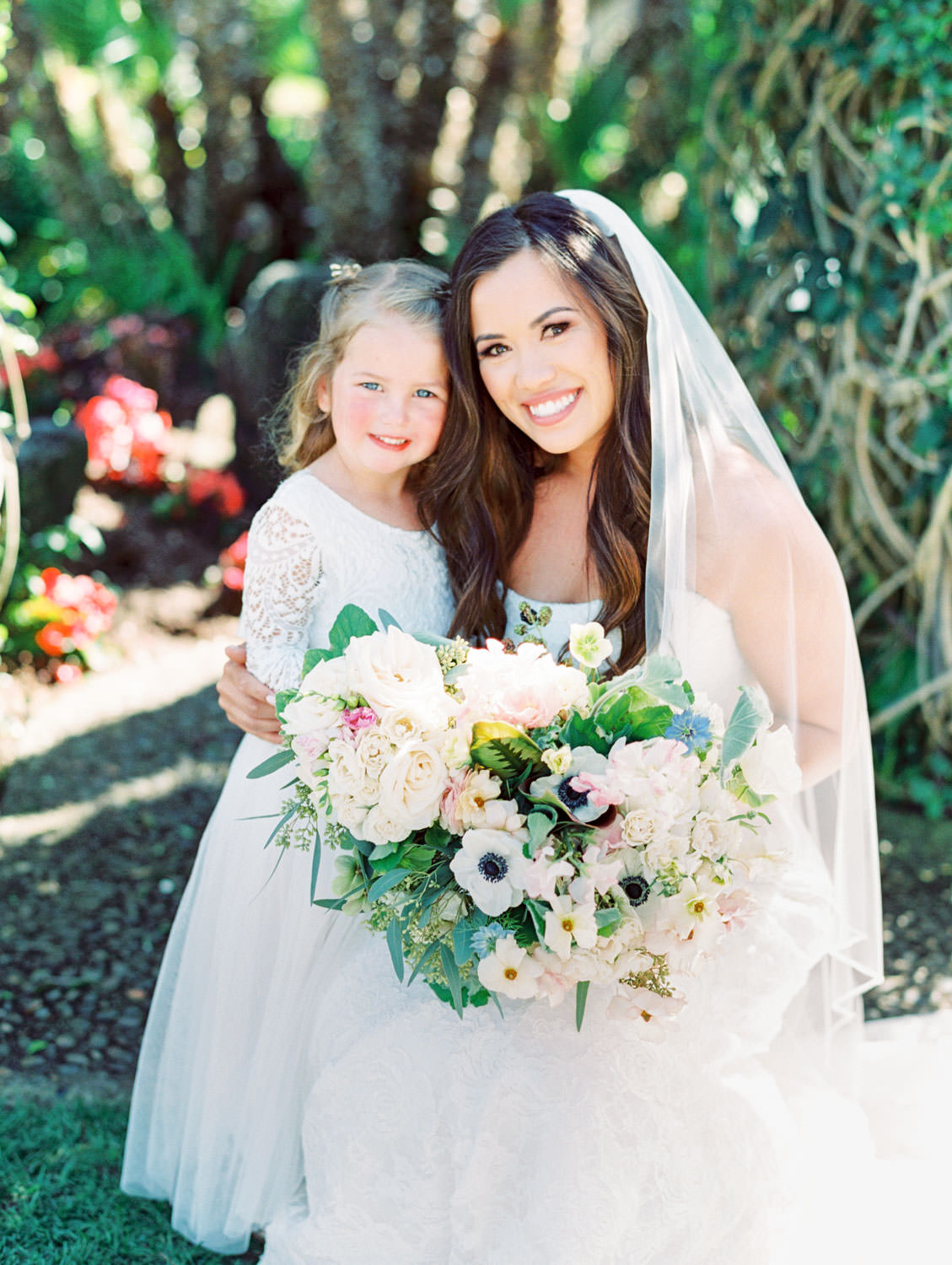 Flower girl with lace white dress and bride in strapless lace gown. Bouquet with anemones, greenery, ivory, and blush flowers captured on film. Wedding at Humphreys Half Moon Inn by Cavin Elizabeth Photography