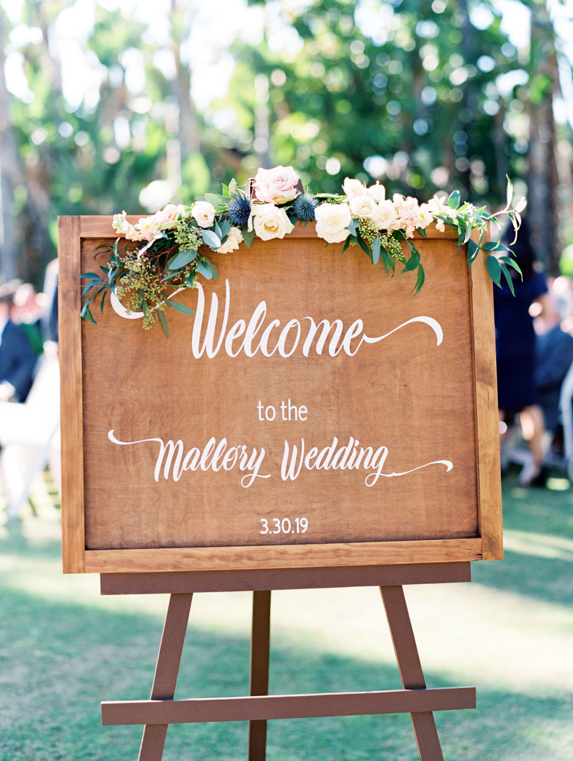 Wooden wedding welcome sign with ivory and blush flowers captured on film. Wedding at Humphreys Half Moon Inn by Cavin Elizabeth Photography