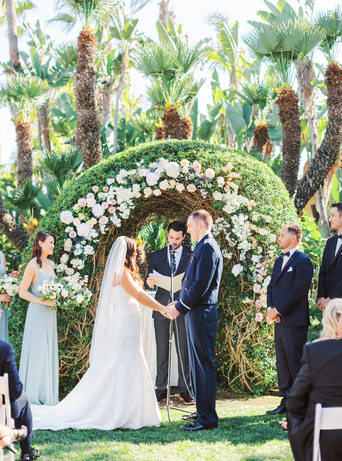 Wedding ceremony captured on film in a garden setting with palm trees and a floral arch with blush and ivory flowers. Wedding at Humphreys Half Moon Inn by Cavin Elizabeth Photography