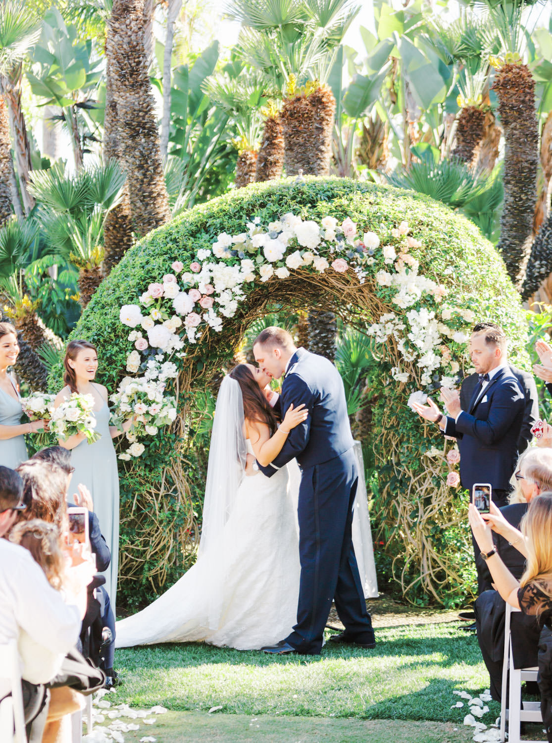 Wedding ceremony first kiss captured on film in a garden setting with palm trees and a floral arch with blush and ivory flowers. Wedding at Humphreys Half Moon Inn by Cavin Elizabeth Photography