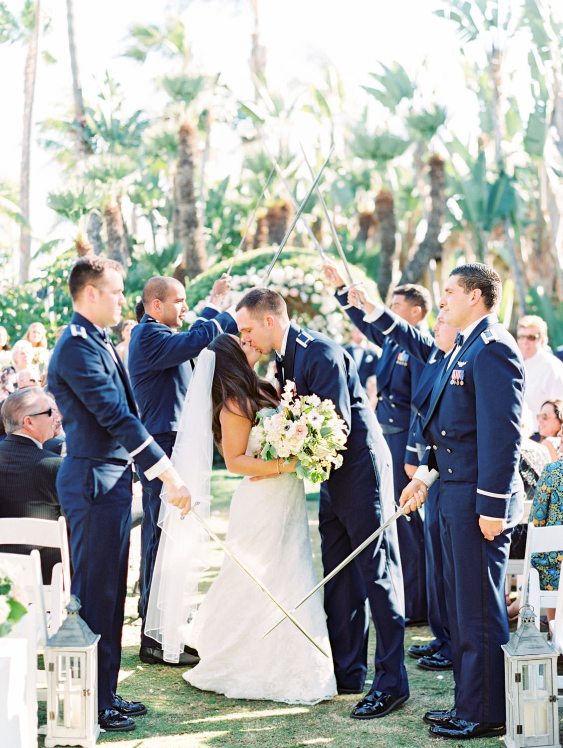 Wedding ceremony Air Force saber arch kiss captured on film in a garden setting with palm trees. Wedding at Humphreys Half Moon Inn by Cavin Elizabeth Photography
