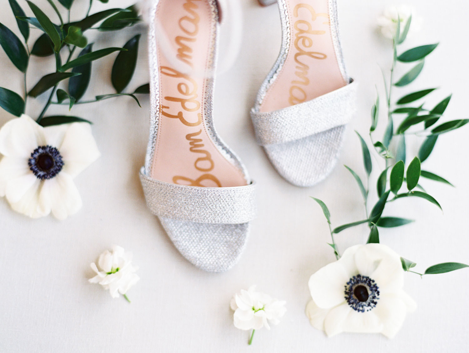 Silver glitter Sam Edelman pumps surrounded by anemones and smilax on film, Wedding at Humphreys Half Moon Inn by Cavin Elizabeth Photography