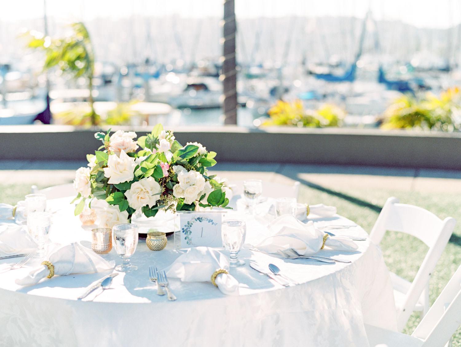 Wedding reception table with white linen and arrangement with ivory and blush roses and greenery captured on film. Wedding at Humphreys Half Moon Inn by Cavin Elizabeth Photography