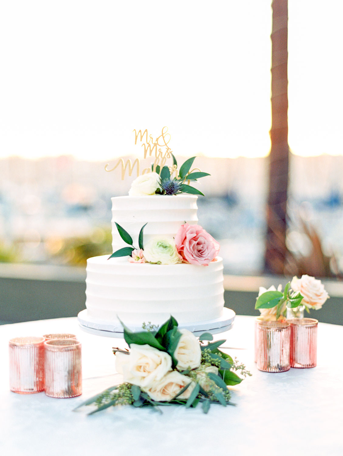 Two tier white classic wedding cake decorated in pink and ivory roses and greenery surrounded by rose gold votives captured on film. Wedding at Humphreys Half Moon Inn by Cavin Elizabeth Photography