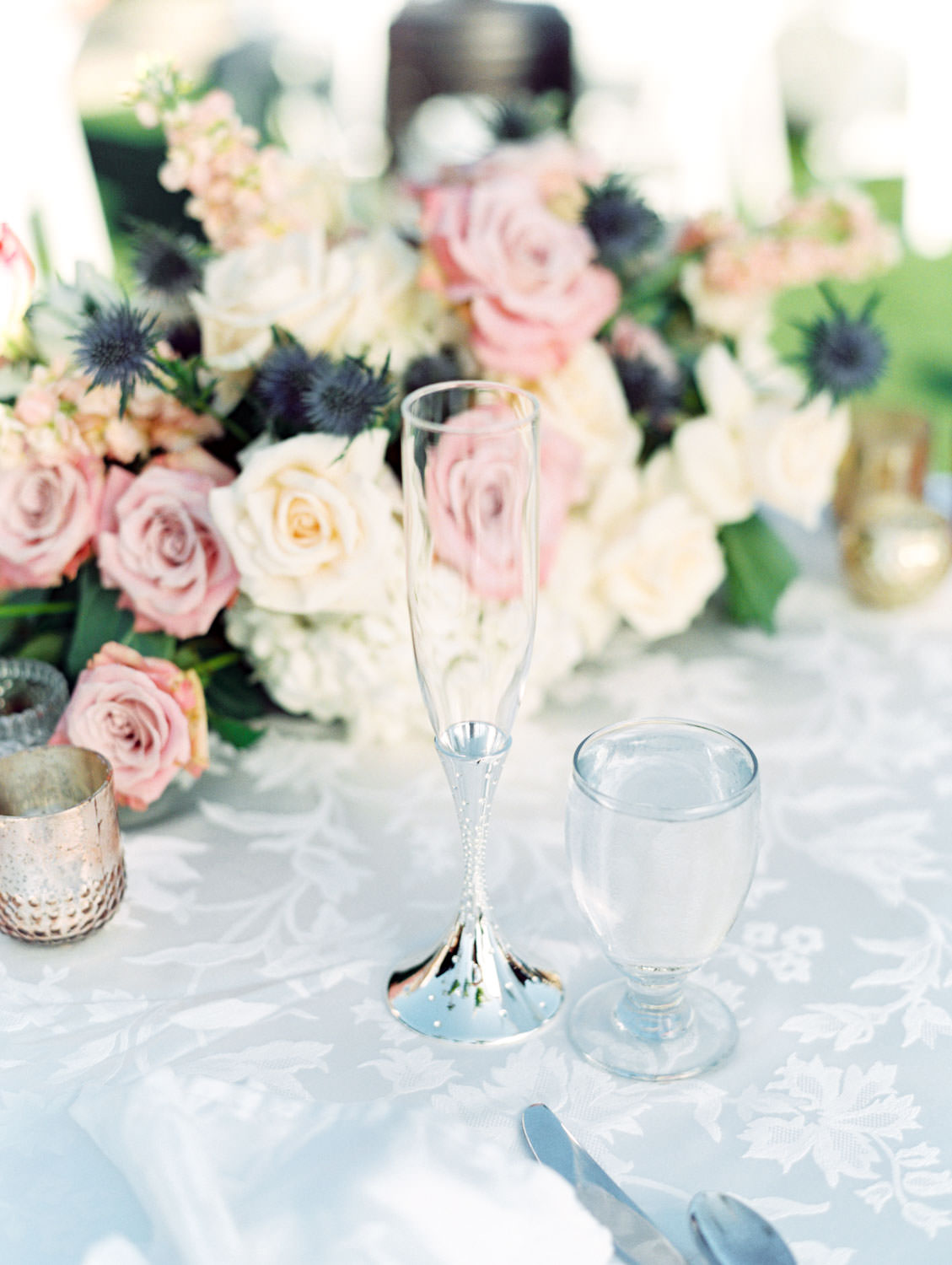 Sweetheart table's champagne glass and centerpiece with pink and ivory roses and greenery surrounded by rose gold votives captured on film. Wedding at Humphreys Half Moon Inn by Cavin Elizabeth Photography