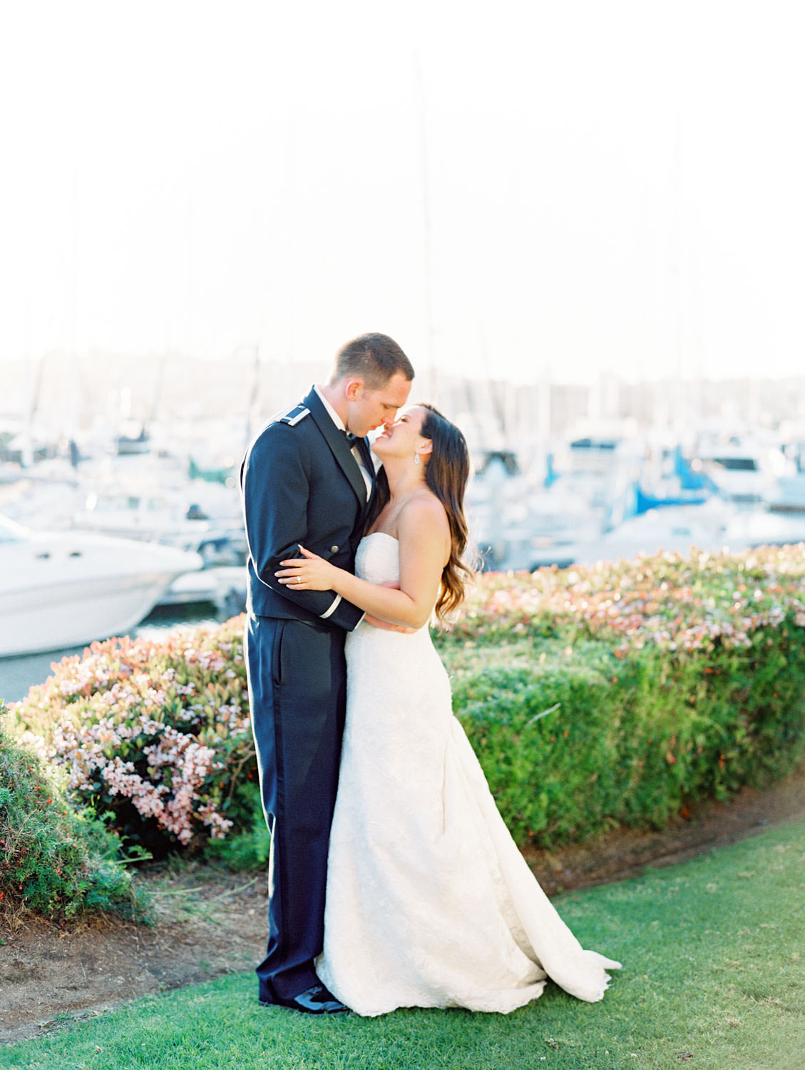 Bride and groom kissing in front of the marina during sunset captured on film. Wedding at Humphreys by Cavin Elizabeth Photography