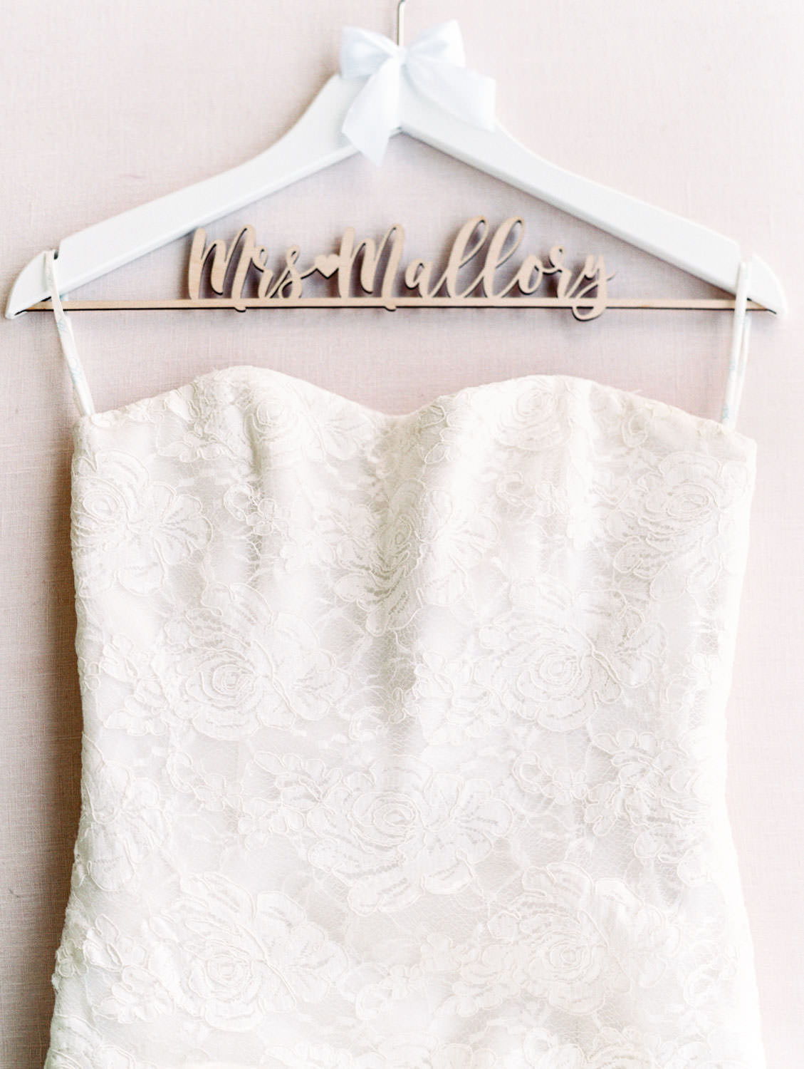 Strapless wedding gown with lace and custom white hanger with wooden laser cut last name on film, Wedding at Humphreys Half Moon Inn by Cavin Elizabeth Photography