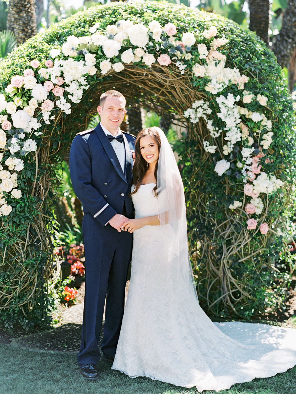 Classic bride and groom portrait in front of floral arch on film. Wedding at Humphreys Half Moon Inn by Cavin Elizabeth Photography