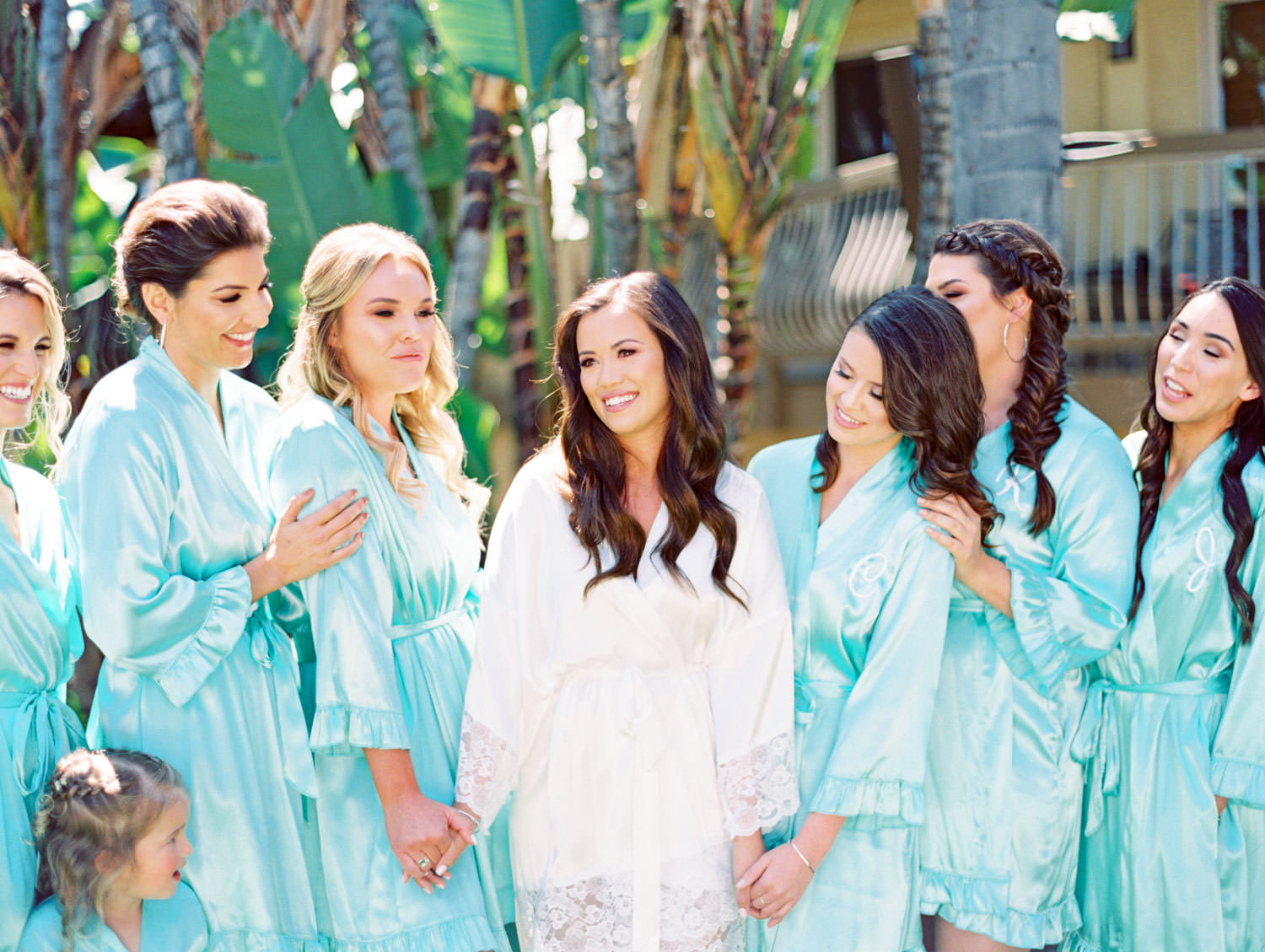Bridal party with turquoise silk robes and bride in white robe outside in front of palm trees on film, Wedding at Humphreys Half Moon Inn by Cavin Elizabeth Photography