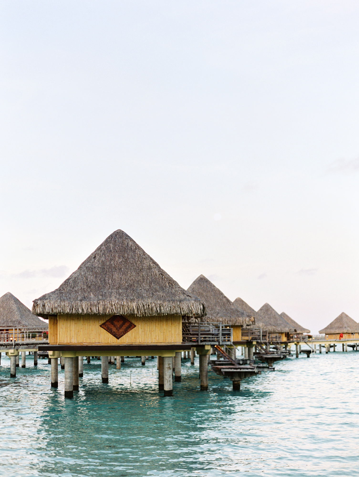 Intercontinental Bora Bora Le Moana bungalows at sunset