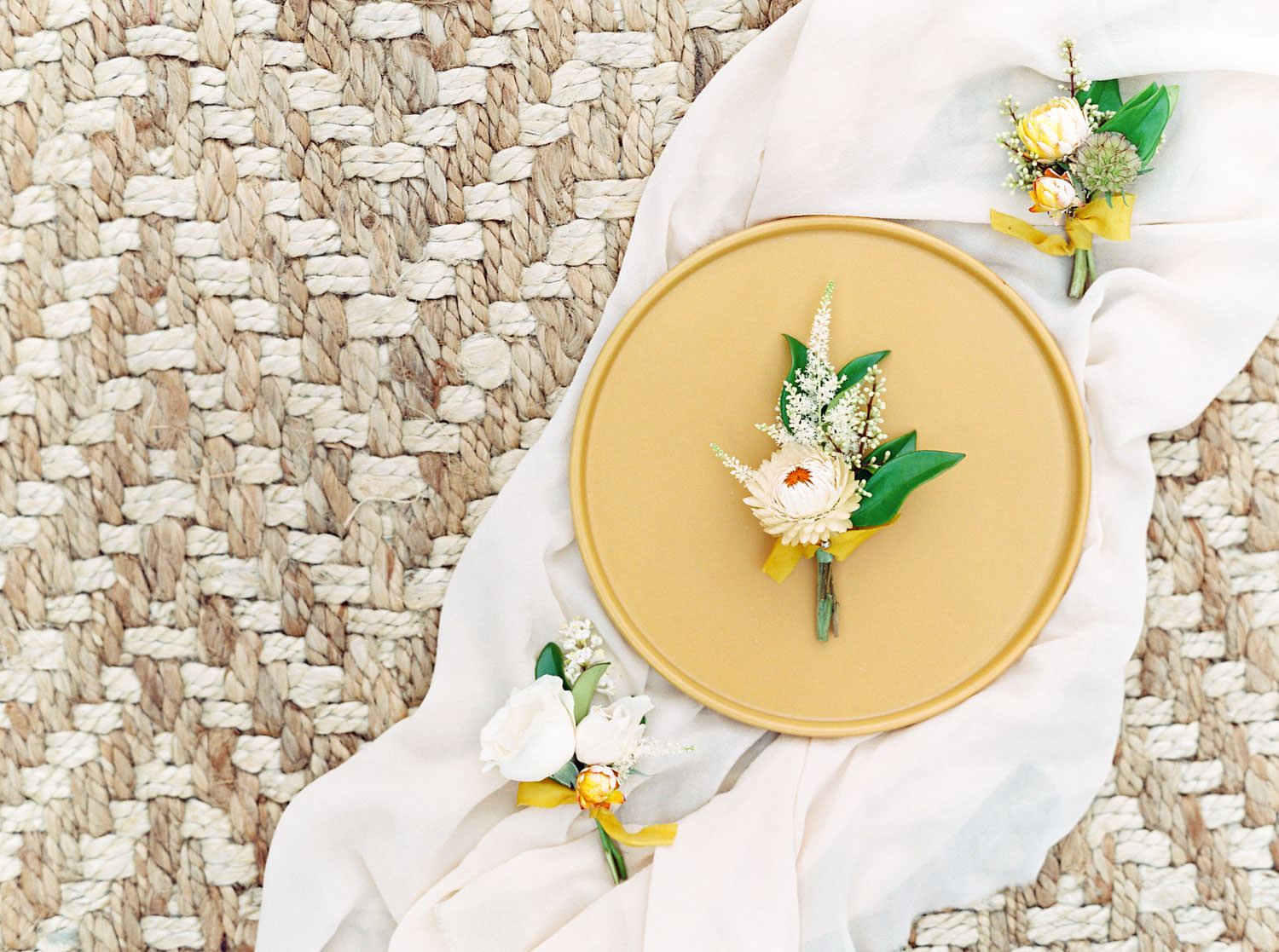 cream boutonnieres with greenery and gold ribbon styled on a golden plate and silk runner, Honey and Beekeeper Inspired Wedding at Rancho Valencia on film by Cavin Elizabeth Photography