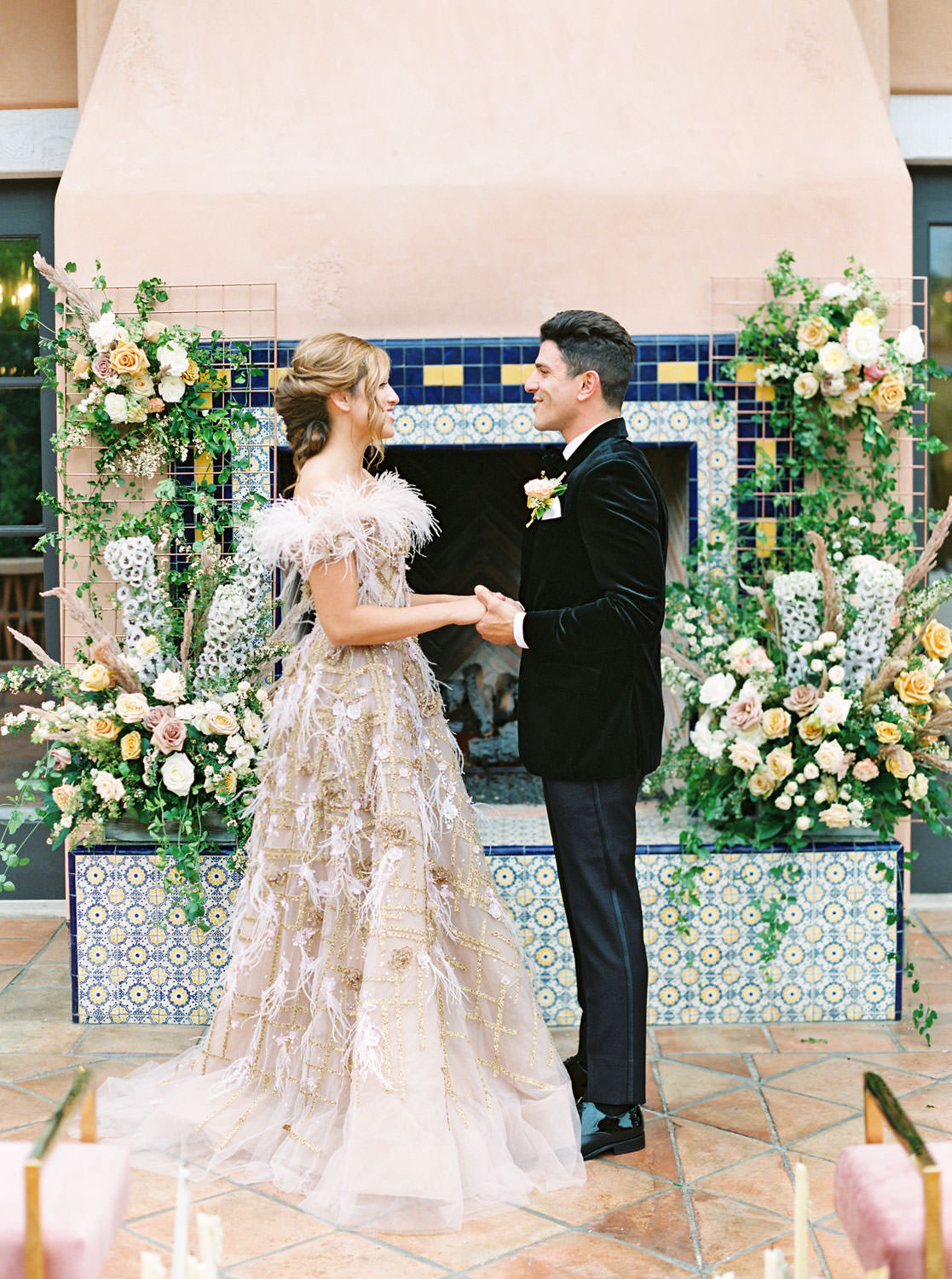 Couple kissing in front of pink fireplace with blue and golden tiles for ceremony backdrop adorned with large floral installations. Marchesa couture gown with blush feathers, gold lines, and floral embellishments. Honey and Beekeeper Inspired Wedding on sunrise terrace patio at Rancho Valencia on film by Cavin Elizabeth Photography