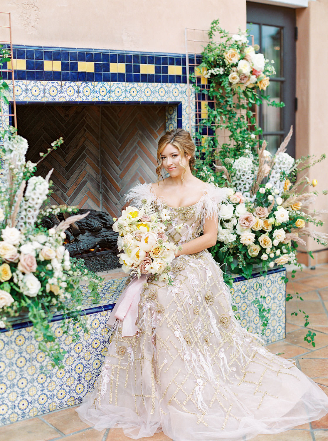 Bride posing with blush, yellow, ivory bouquet in front of pink fireplace with blue and golden tiles for ceremony backdrop adorned with large floral installations. Marchesa couture gown with blush feathers, gold lines, and floral embellishments. Honey and Beekeeper Inspired Wedding on sunrise terrace patio at Rancho Valencia on film by Cavin Elizabeth Photography