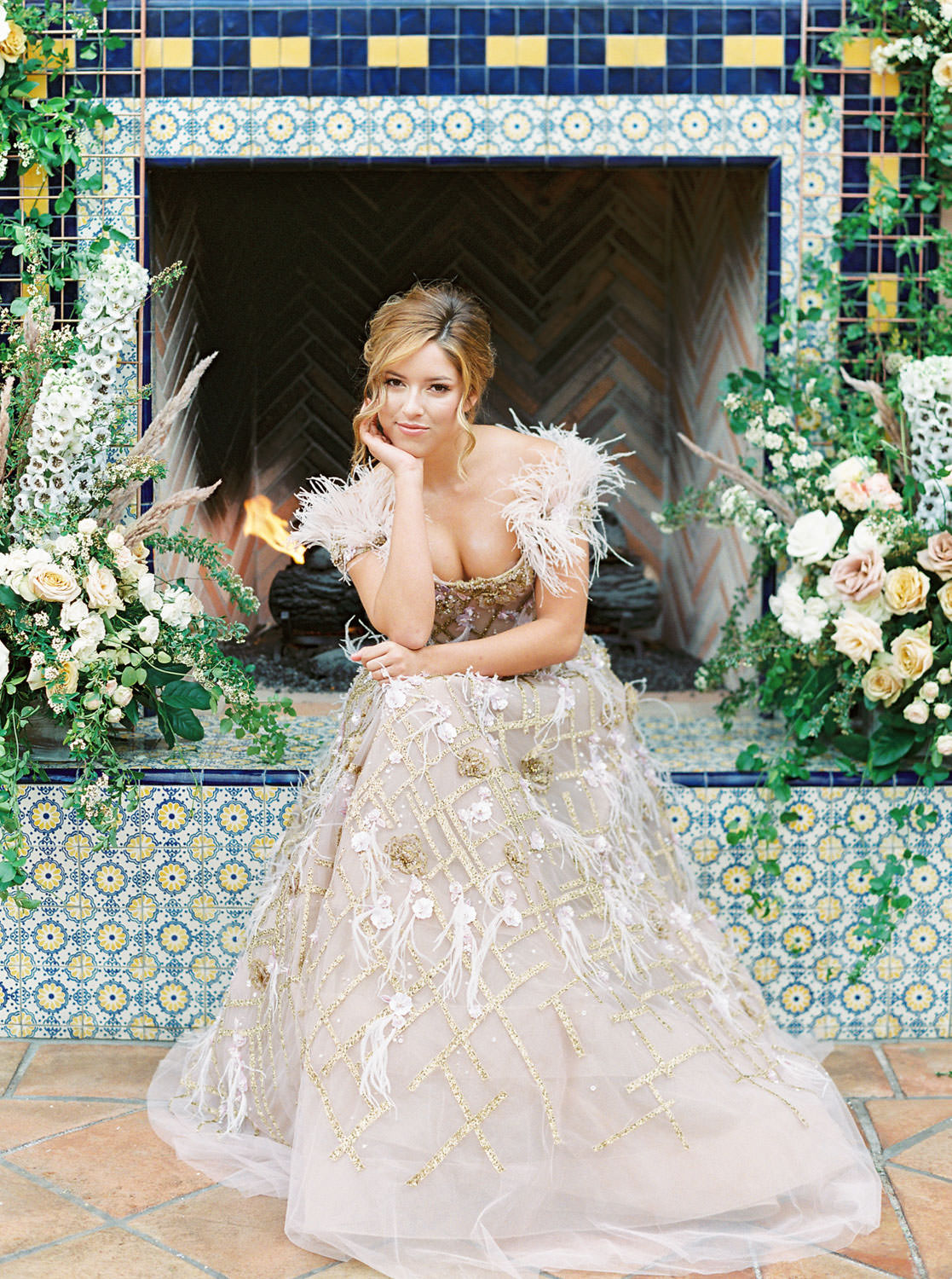 Bride posing in front of pink fireplace with blue and golden tiles for ceremony backdrop adorned with large floral installations. Marchesa couture gown with blush feathers, gold lines, and floral embellishments. Honey and Beekeeper Inspired Wedding on sunrise terrace patio at Rancho Valencia on film by Cavin Elizabeth Photography