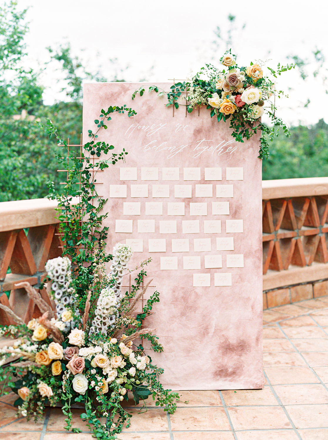 Mauve blush painterly escort card display with large floral installations in green, mauve, ivory, yellow, and gold flowers. Ivory place cards with mauve calligraphy. Honey and Beekeeper Inspired Wedding on sunrise terrace patio at Rancho Valencia on film by Cavin Elizabeth Photography
