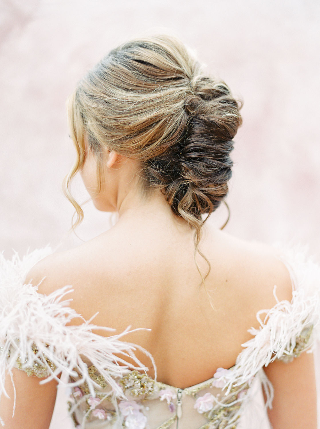 Bridal updo long twist wearing a Marchesa couture gown with blush feathers, gold lines, and floral embellishments. Honey and Beekeeper Inspired Wedding on sunrise terrace patio at Rancho Valencia on film by Cavin Elizabeth Photography