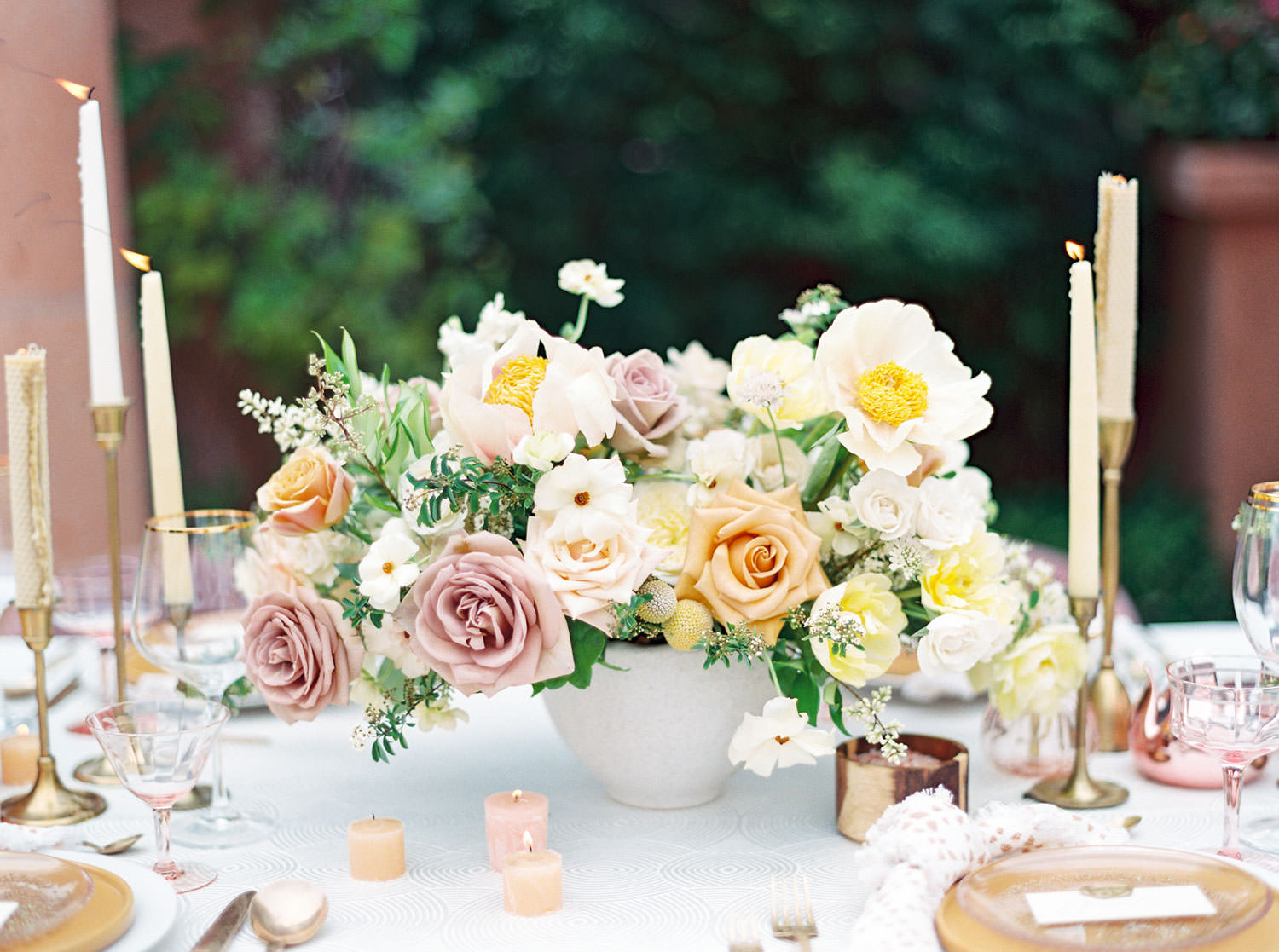Reception table with textured ivory linen, blush mauve velvet chairs, golden taper candles, golden plates and flatware, and lush centerpieces with mauve, ivory, and melon roses with greenery. Honey and Beekeeper Inspired Wedding at Rancho Valencia on film by Cavin Elizabeth Photography